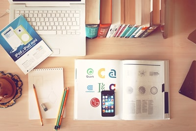 books, pencils, laptop, and iphone on a desk