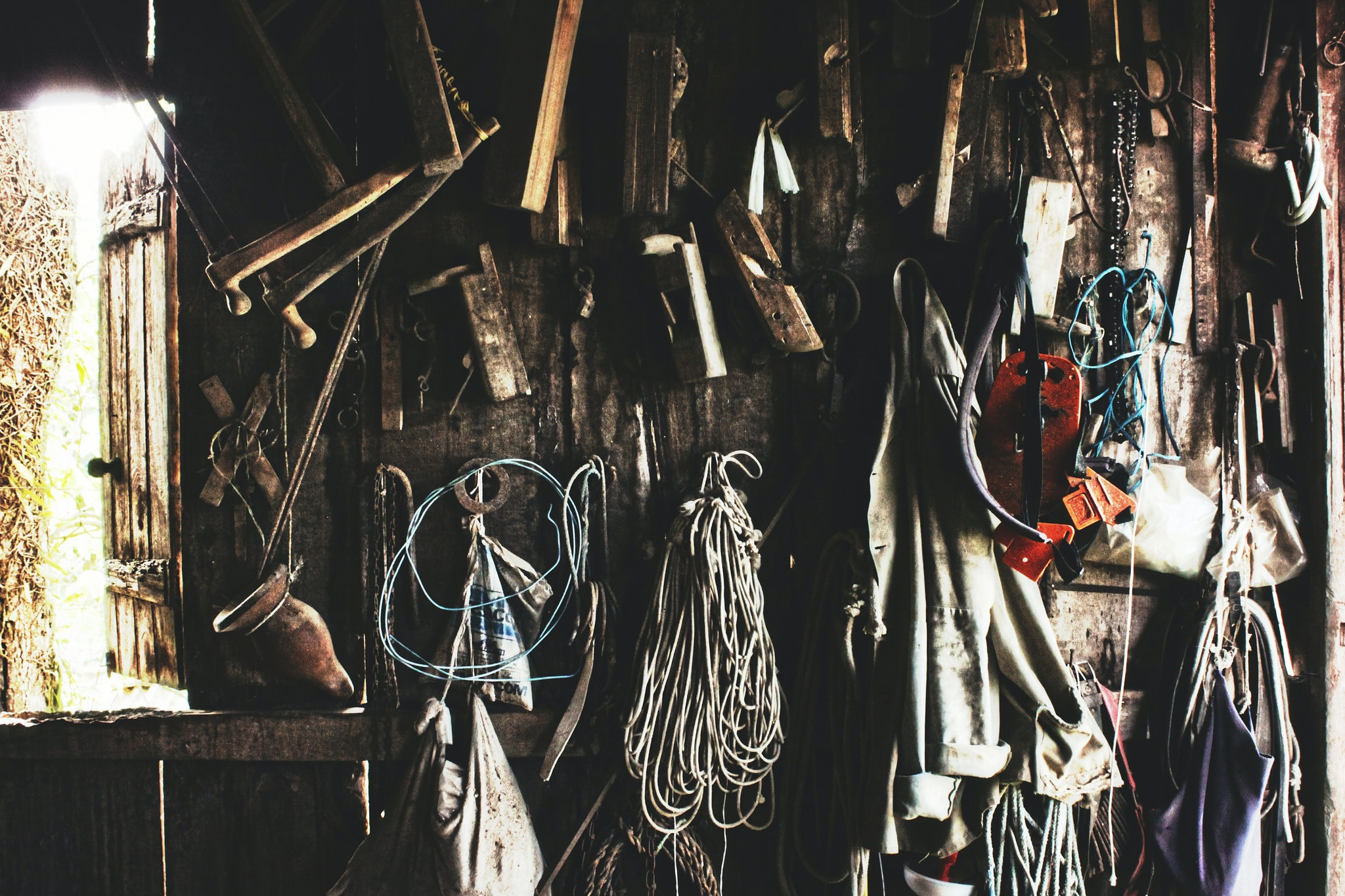 Various tools and ropes hanging from a wall in a workshop