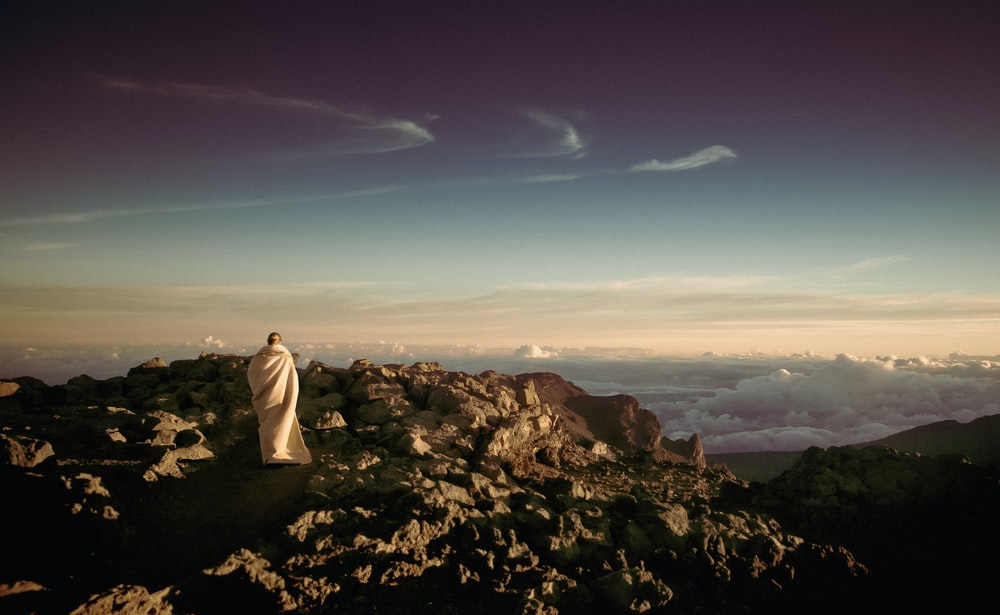 person wearing white robe on top of rocky mountain