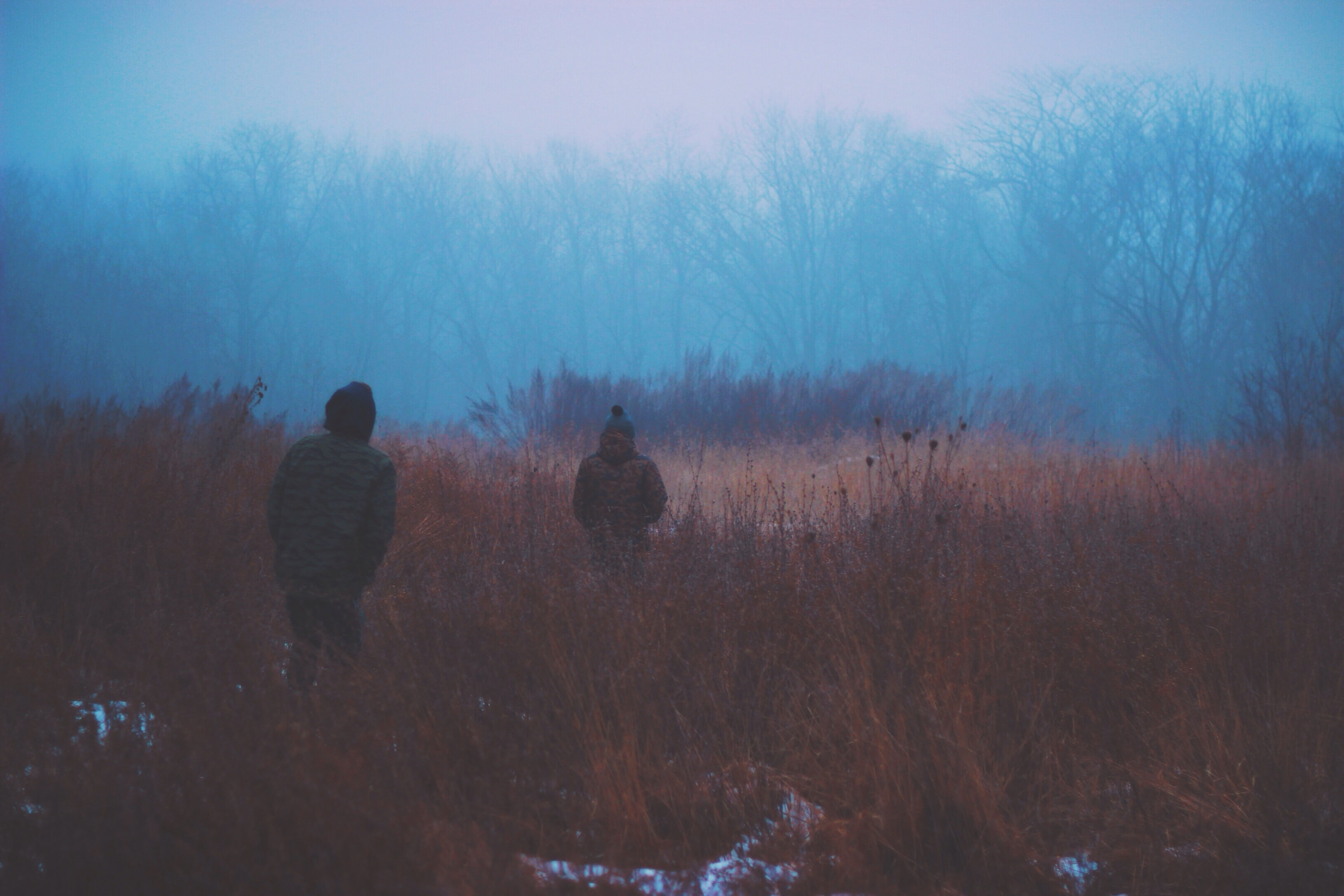 Two people walking through brown grass on a cold evening