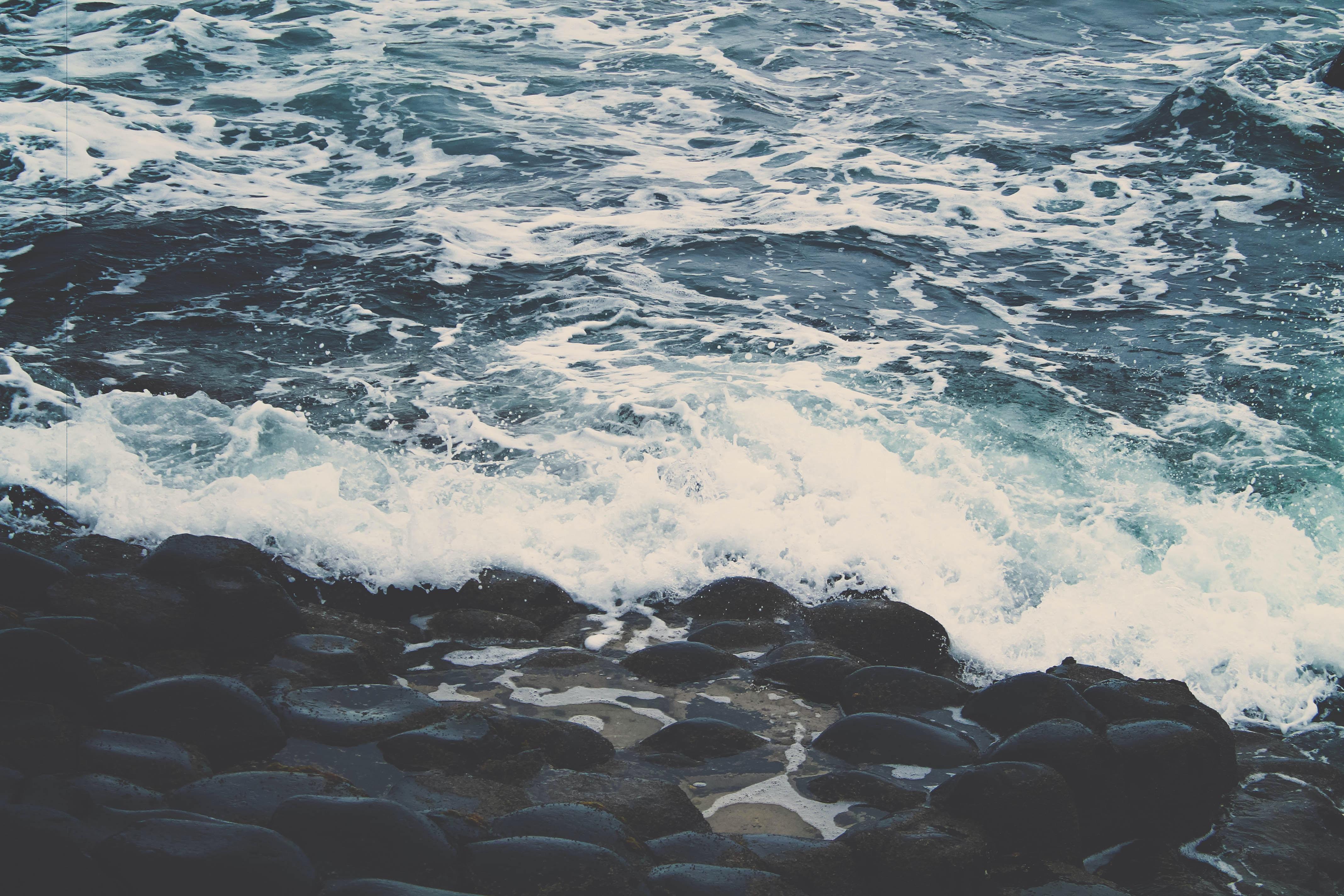 sea waves splashing through stone