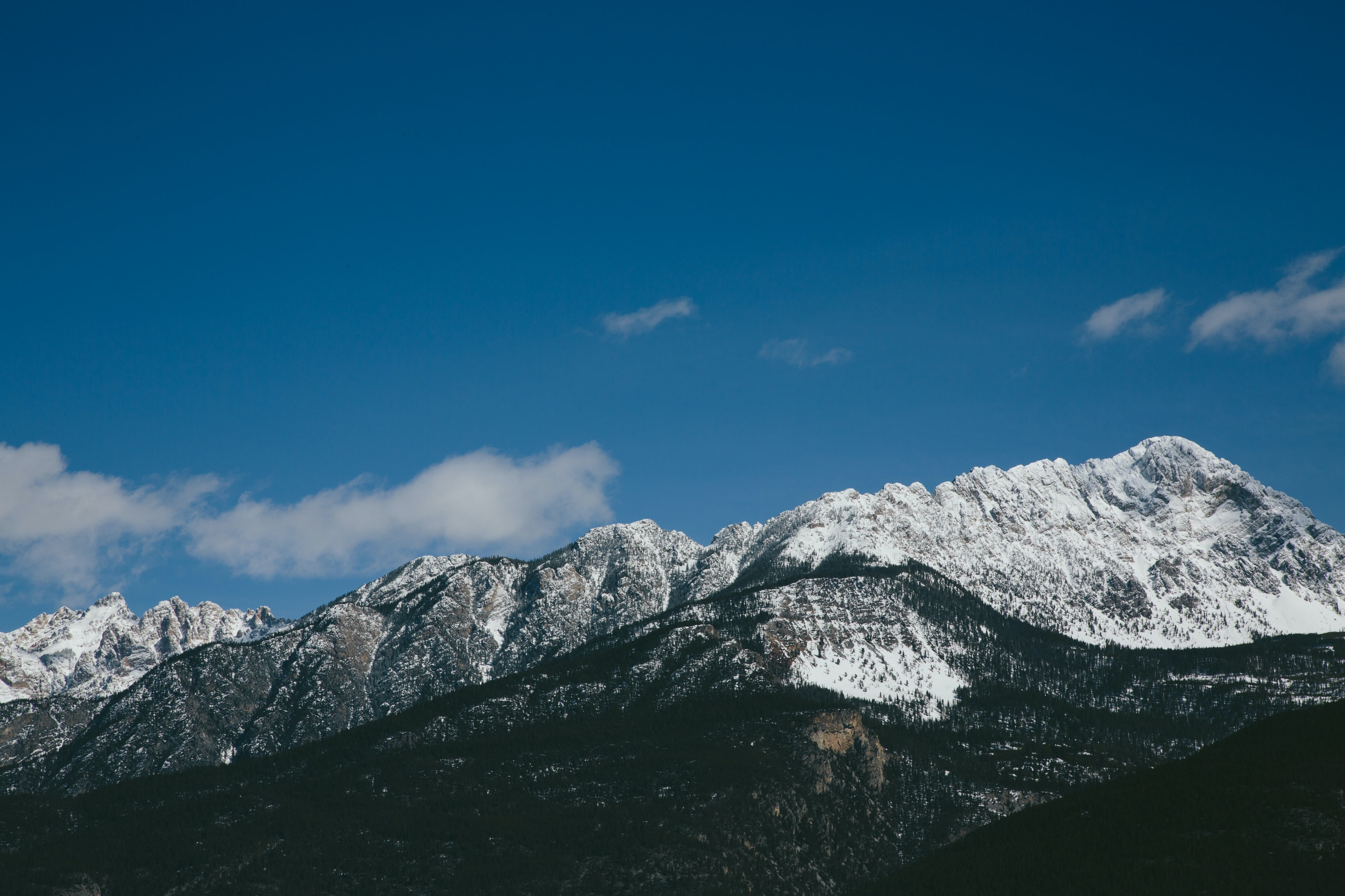 A long mountain ridge crowned with a tall snow-topped peak