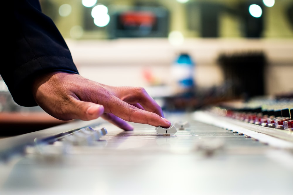 person holding mixing console