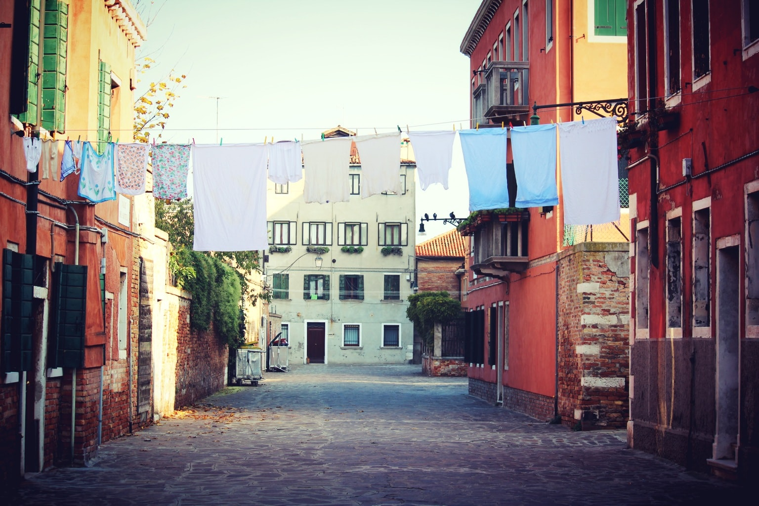 Street-view of colorful houses with clotheslines full of drying clothes across the street