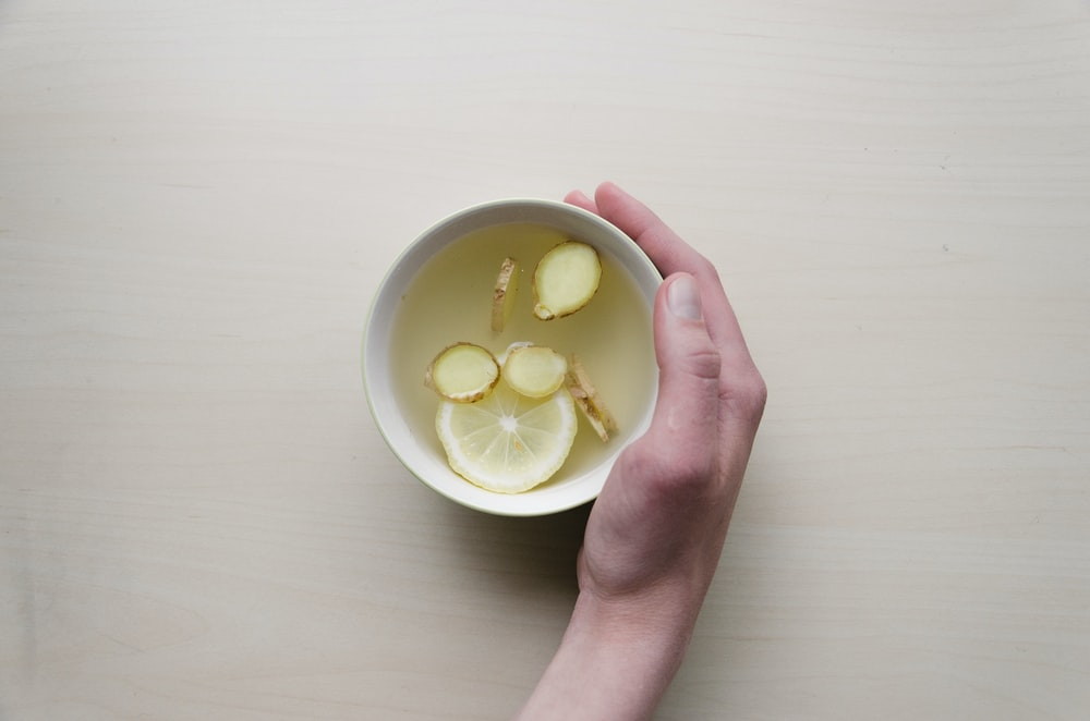 person holding white bowl with sliced lime and ginger inside