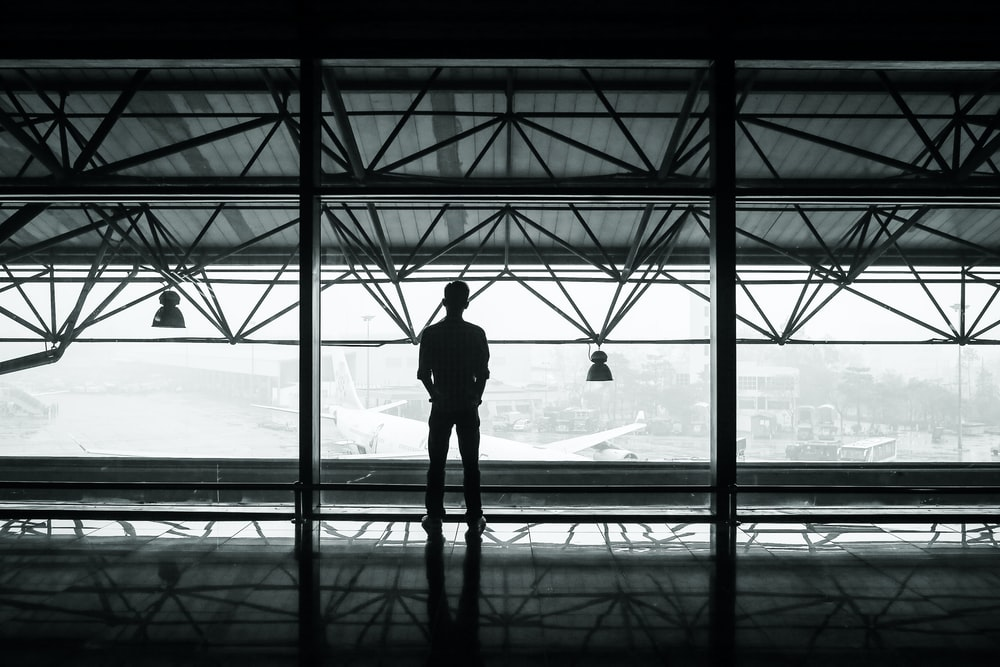 silhouette of man standing between two posts