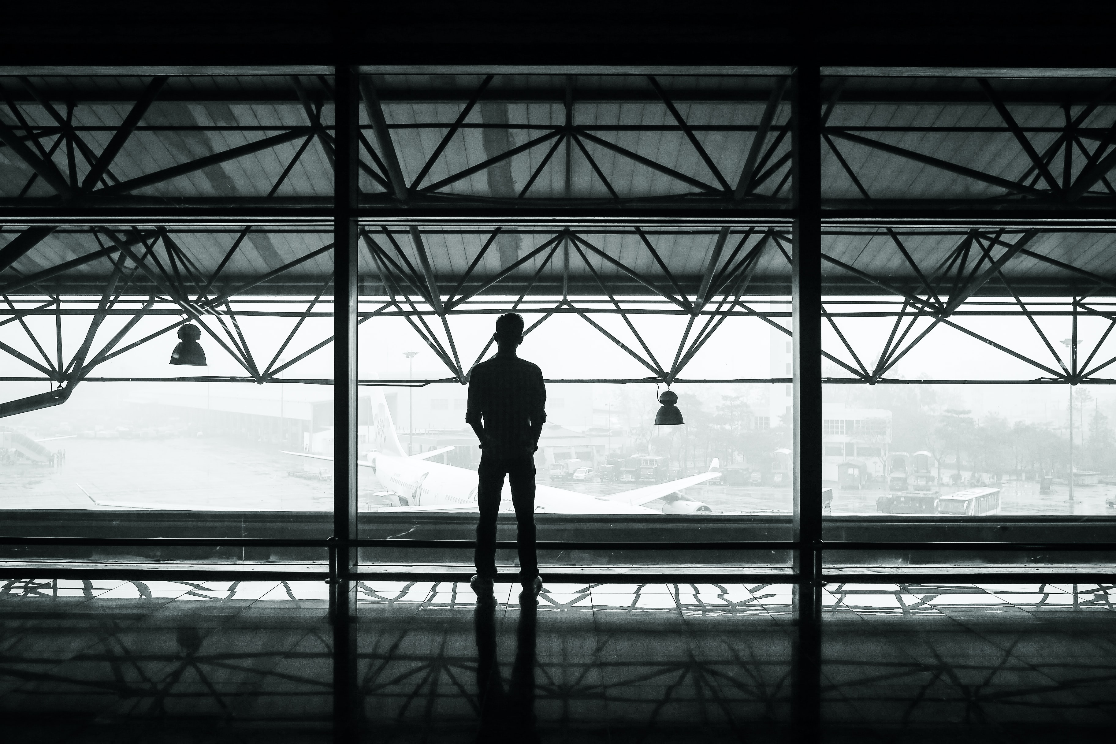 A silhouetted man looks at a plane out an airport window