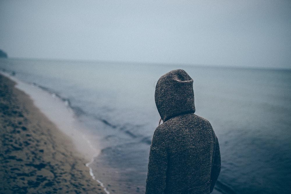 person standing beside seashore