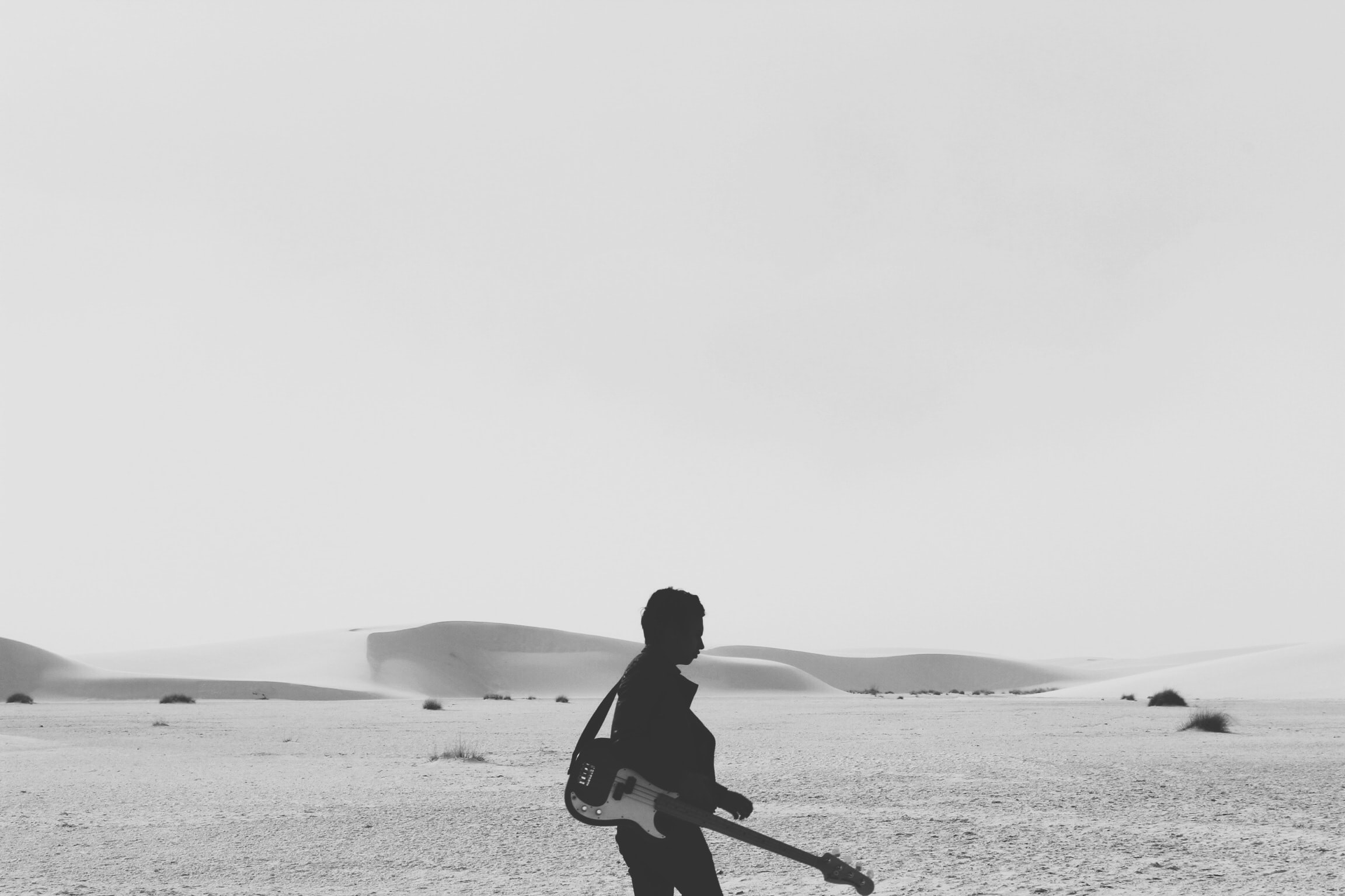 A black-and-white photo of a man with a guitar silhouetted against sand dunes in a desert