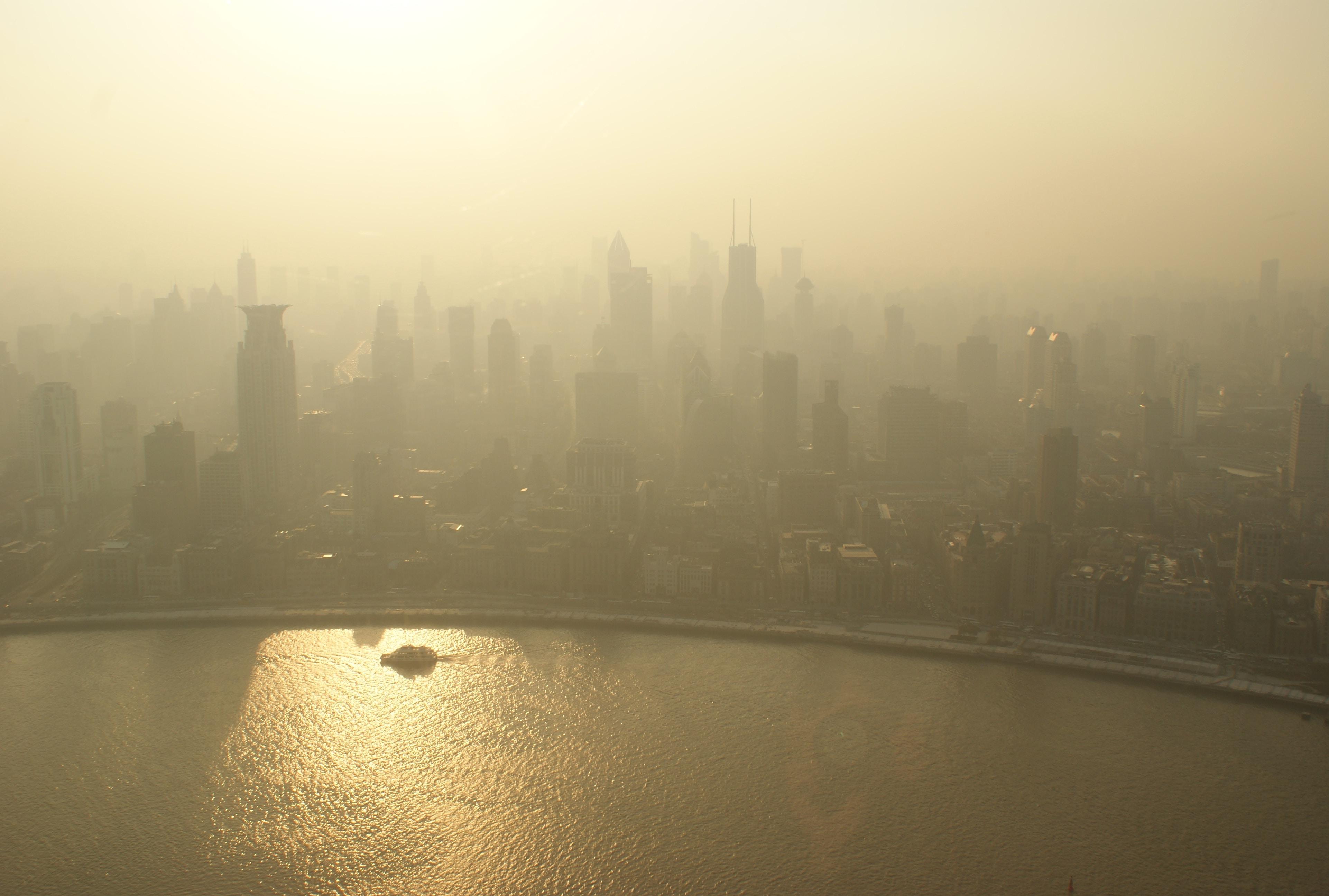 A hazy skyline of a city on a river