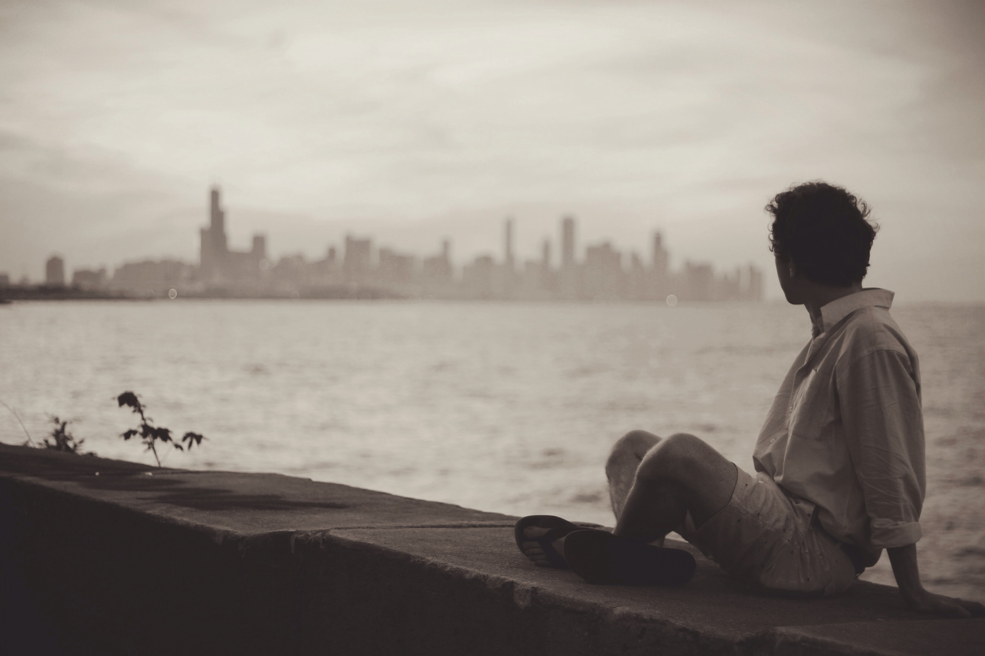 Man sitting on stone wall in front of water and city skyline