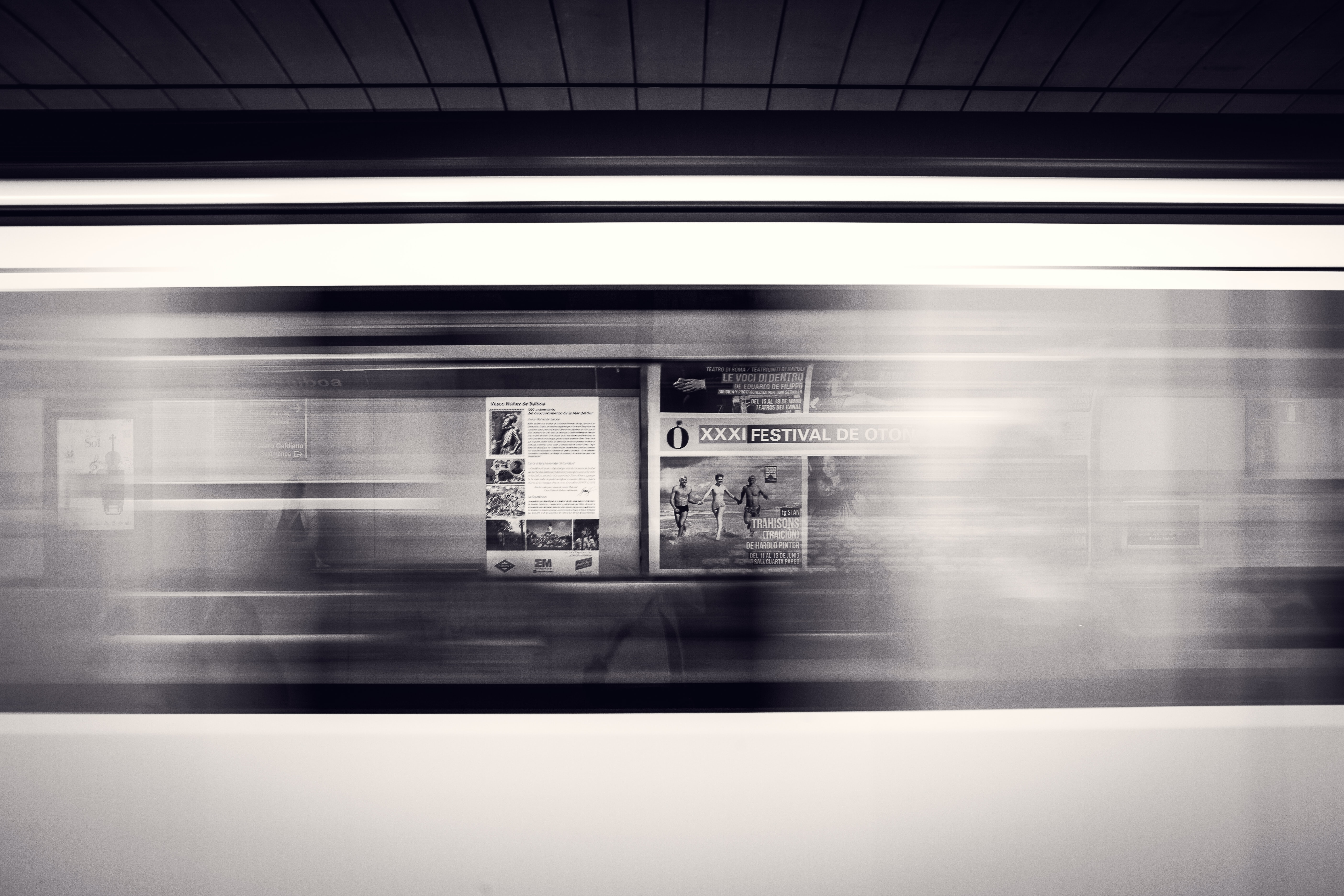 A long-exposure shot of a moving subway train and advertisement posters at the station