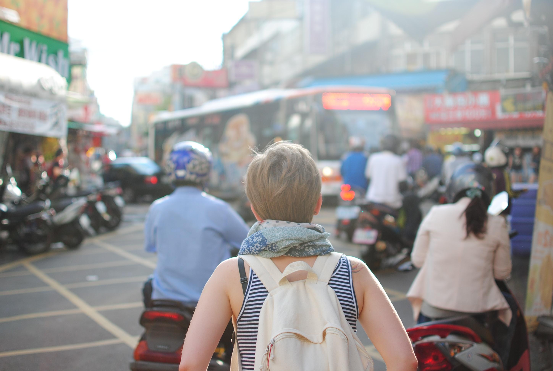 woman wearing backpack walking on road