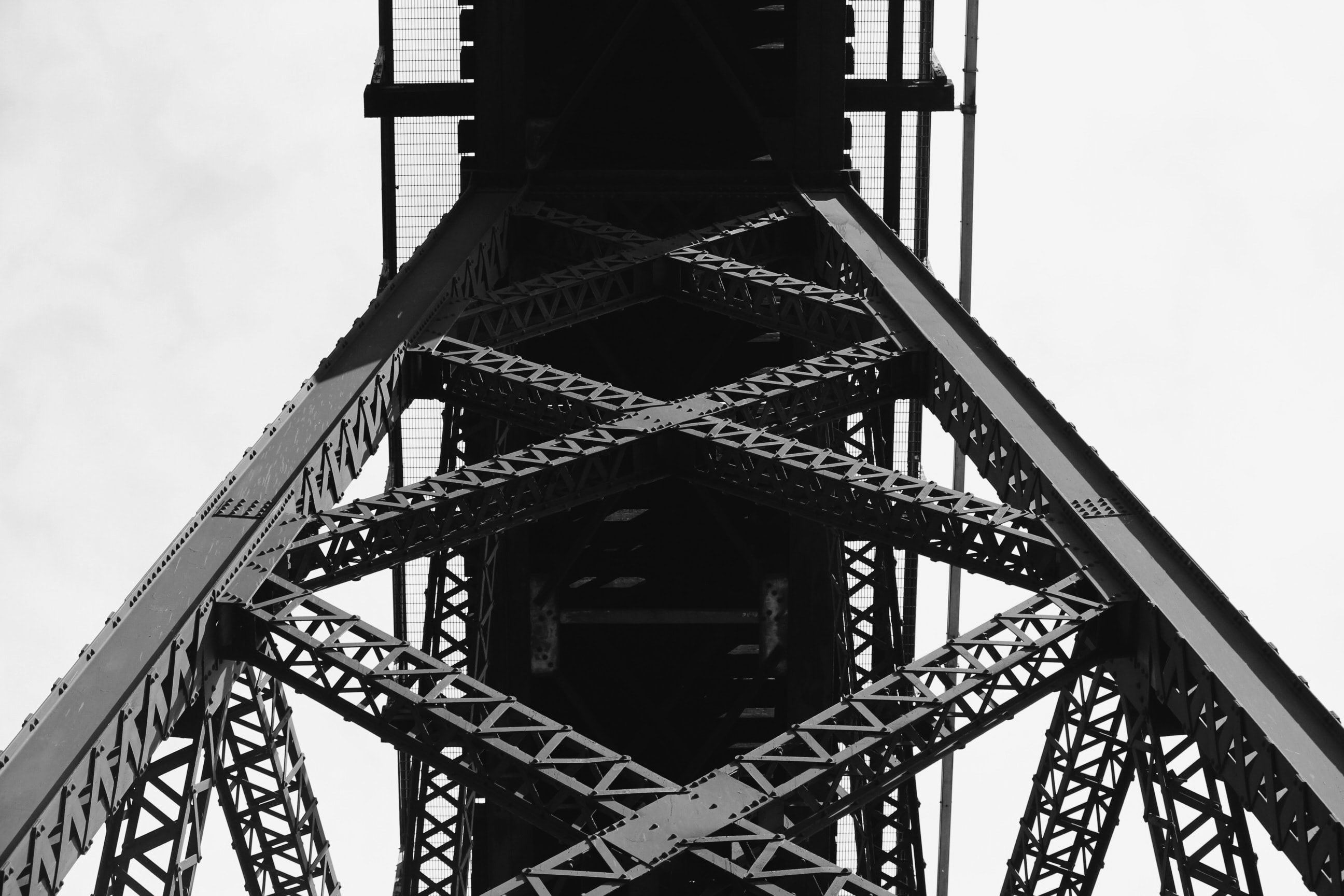 low angle and grayscale photography of metal bridge