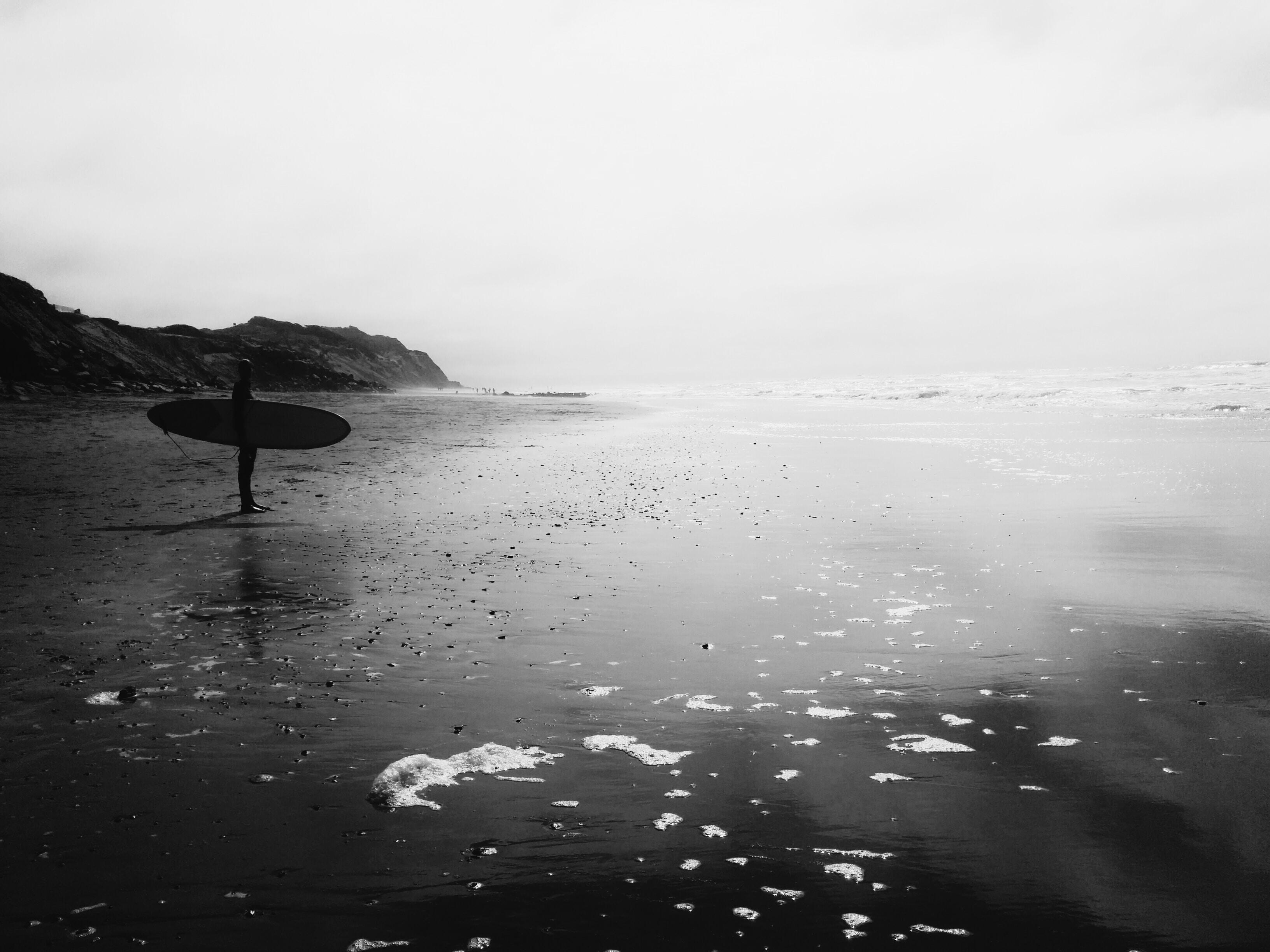 man holding skimboard near sea