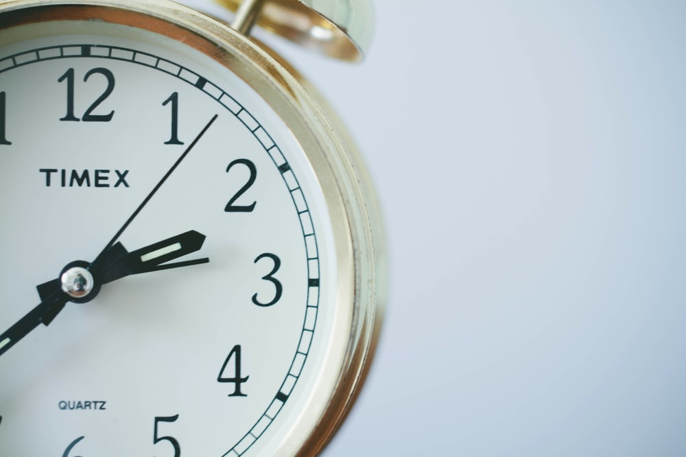 round Timex analog clock at 2:33