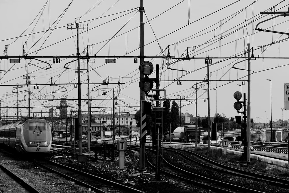 grayscale photo of black posts during cloudy season