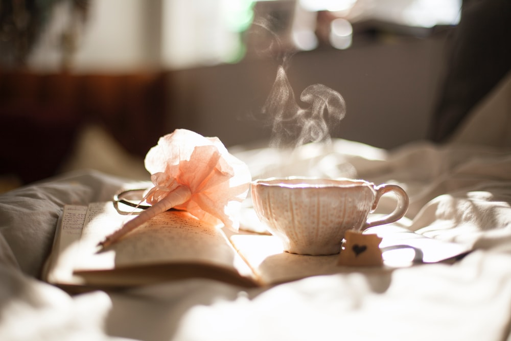 A beautiful ceramic teacup placed on a diary while the tea evaporates as steam