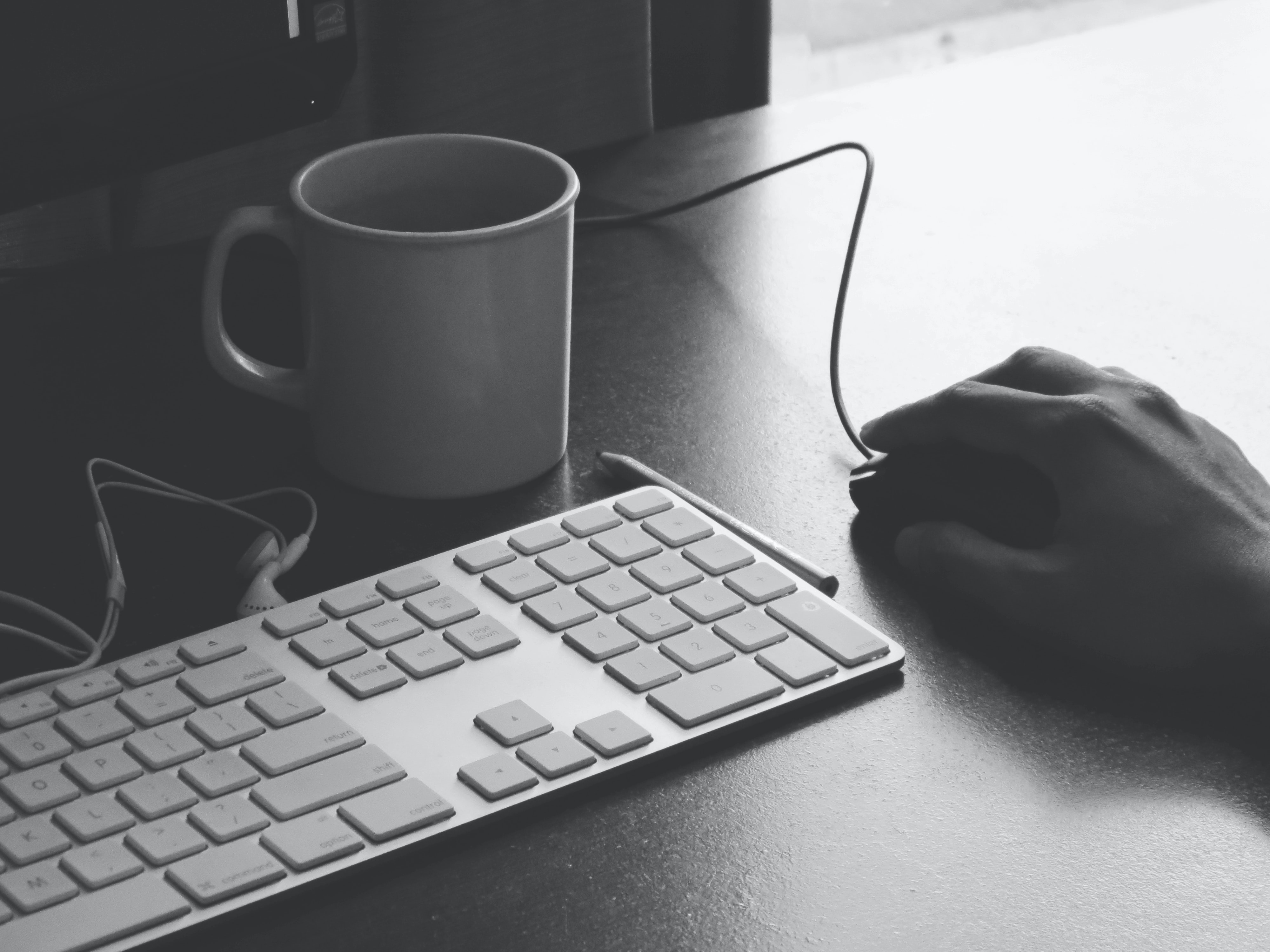 A black and white image of a keyboard, computer, teacup, and a hand holding a mouse in an office setting
