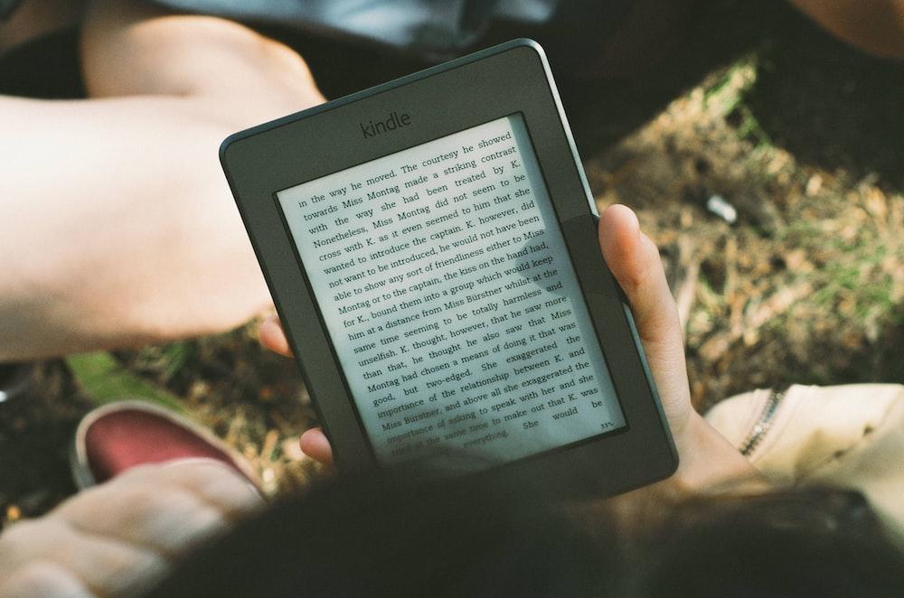 person holding black Amazon Kindle e-book reader