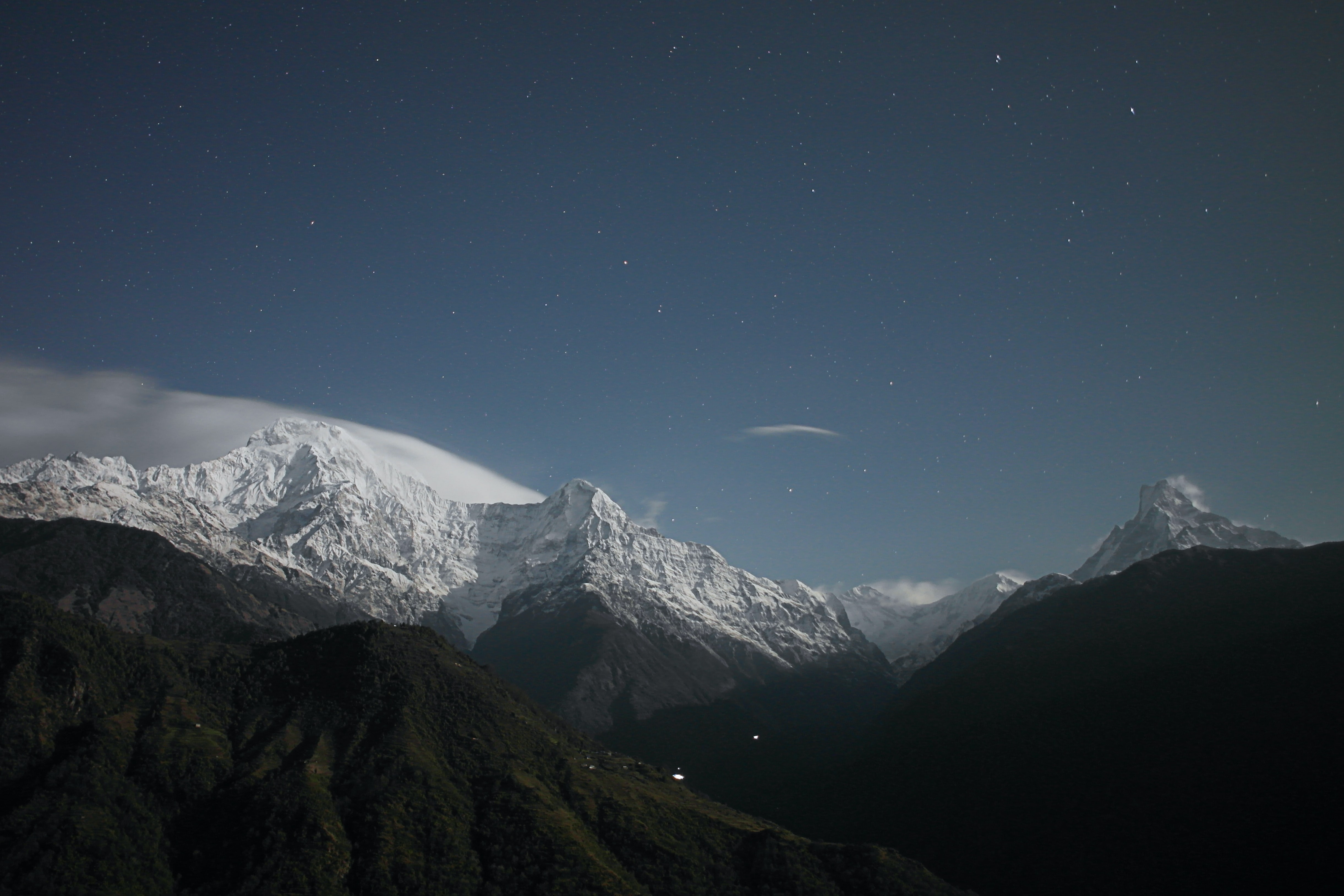 Tall snow-covered mountain peaks under a starry sky
