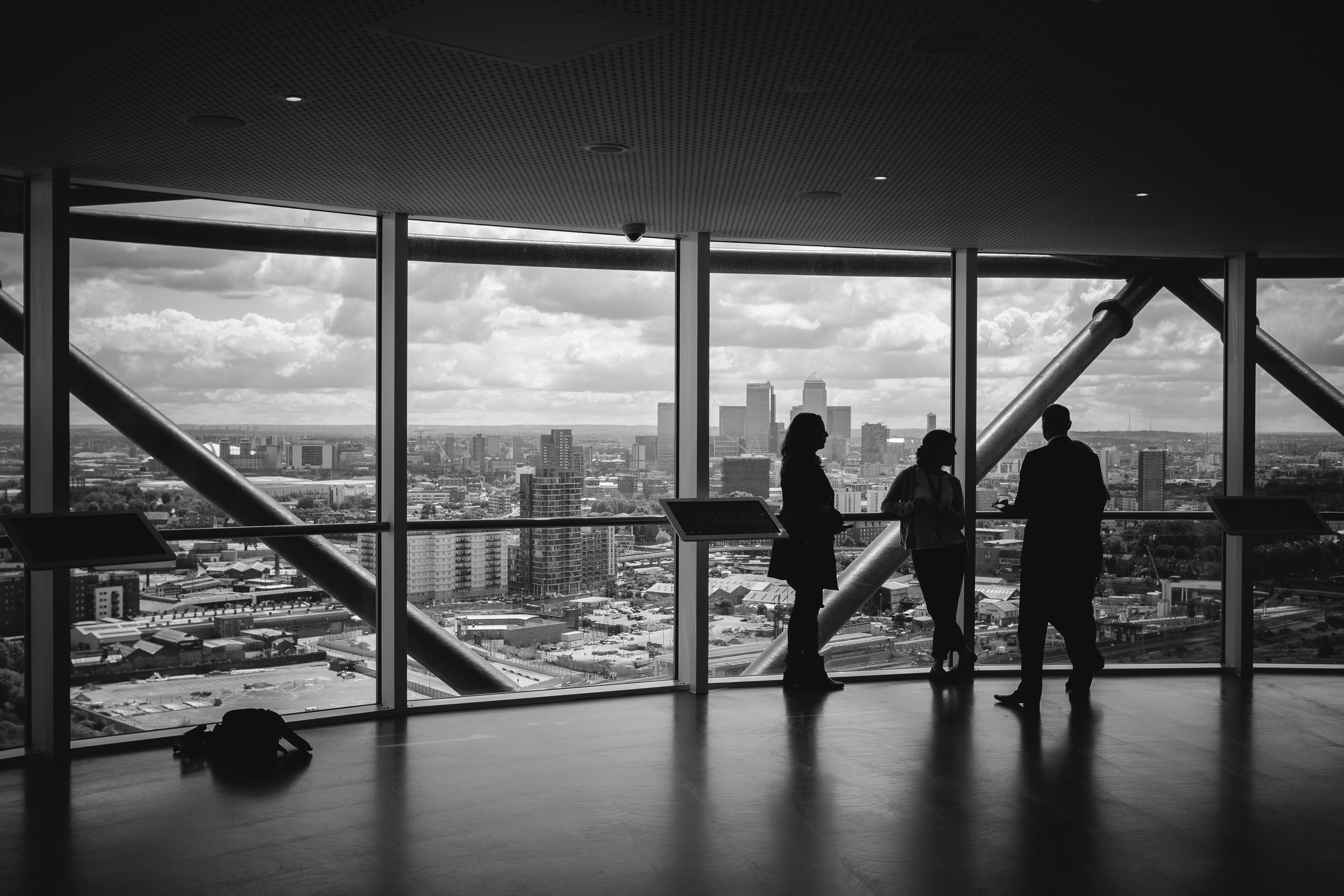 A group of individuals having a meeting near a transparent glass showing beautiful city view.