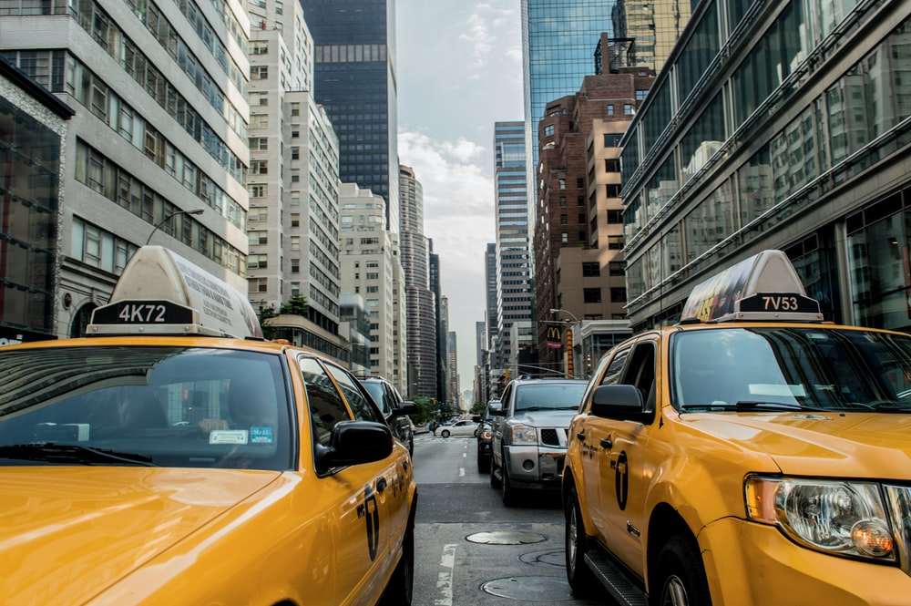 two yellow cars between buildings