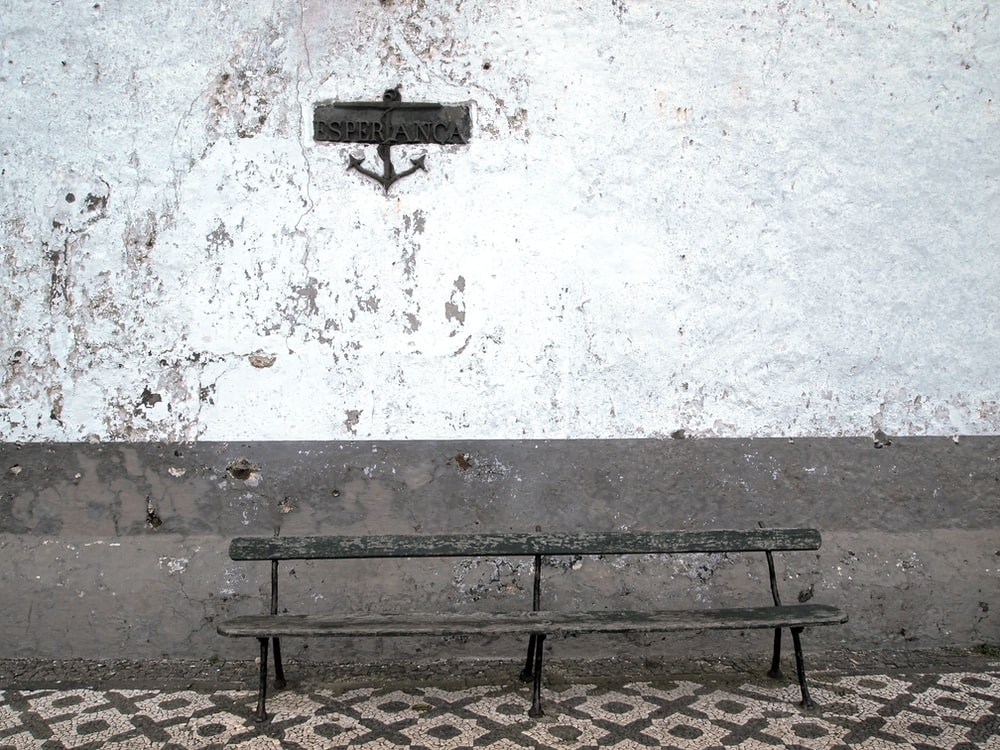 brown steel bench beside wall