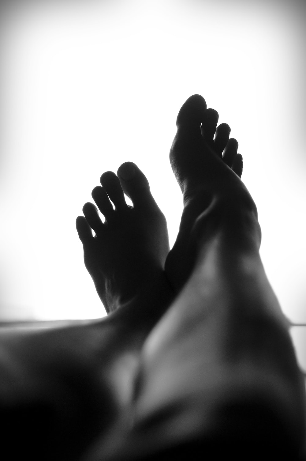 silhouette of person's feet against white background
