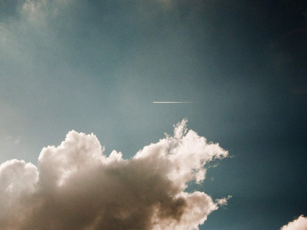 photo of contrail during cloudy daytime
