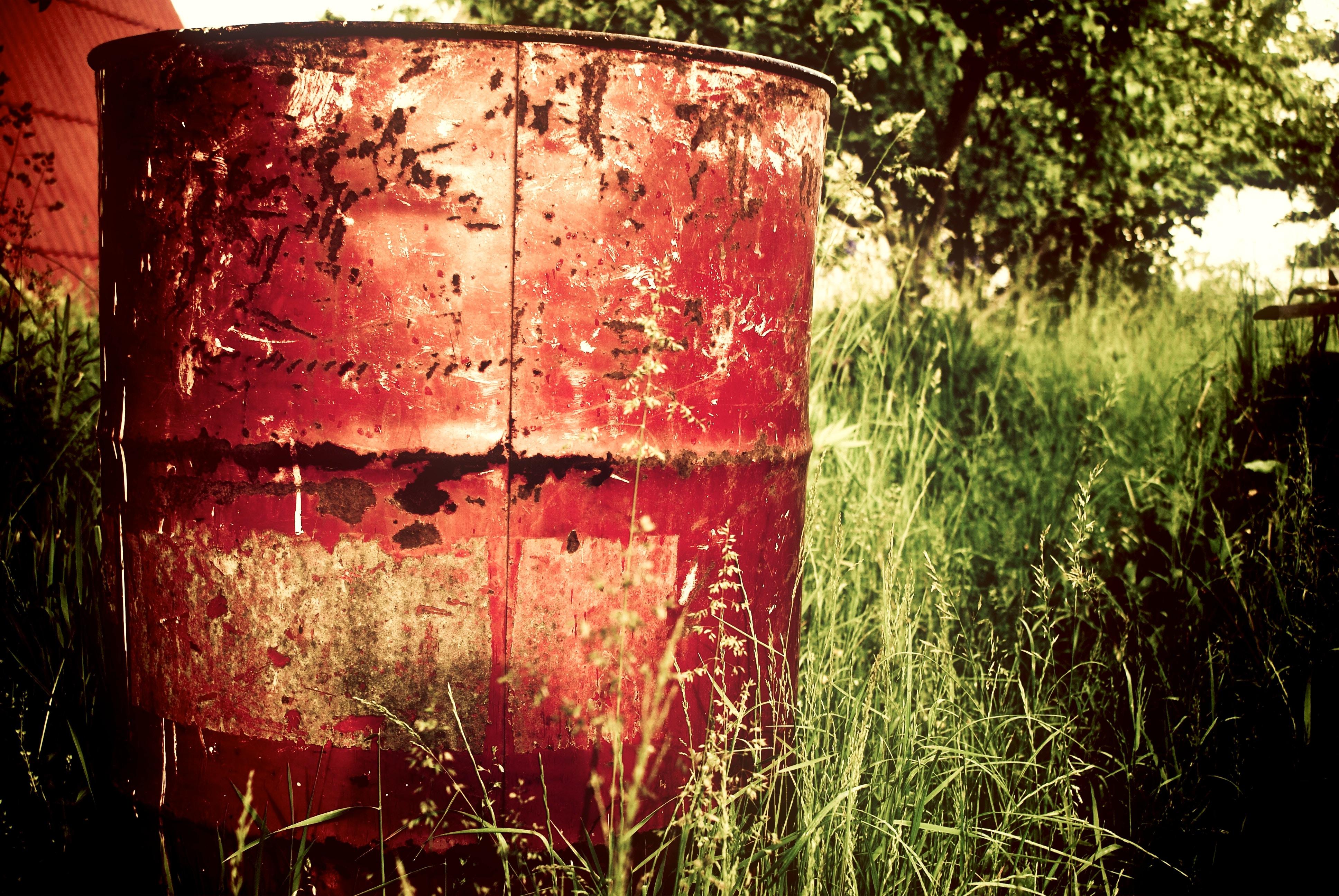 brown metal barrel on grass field