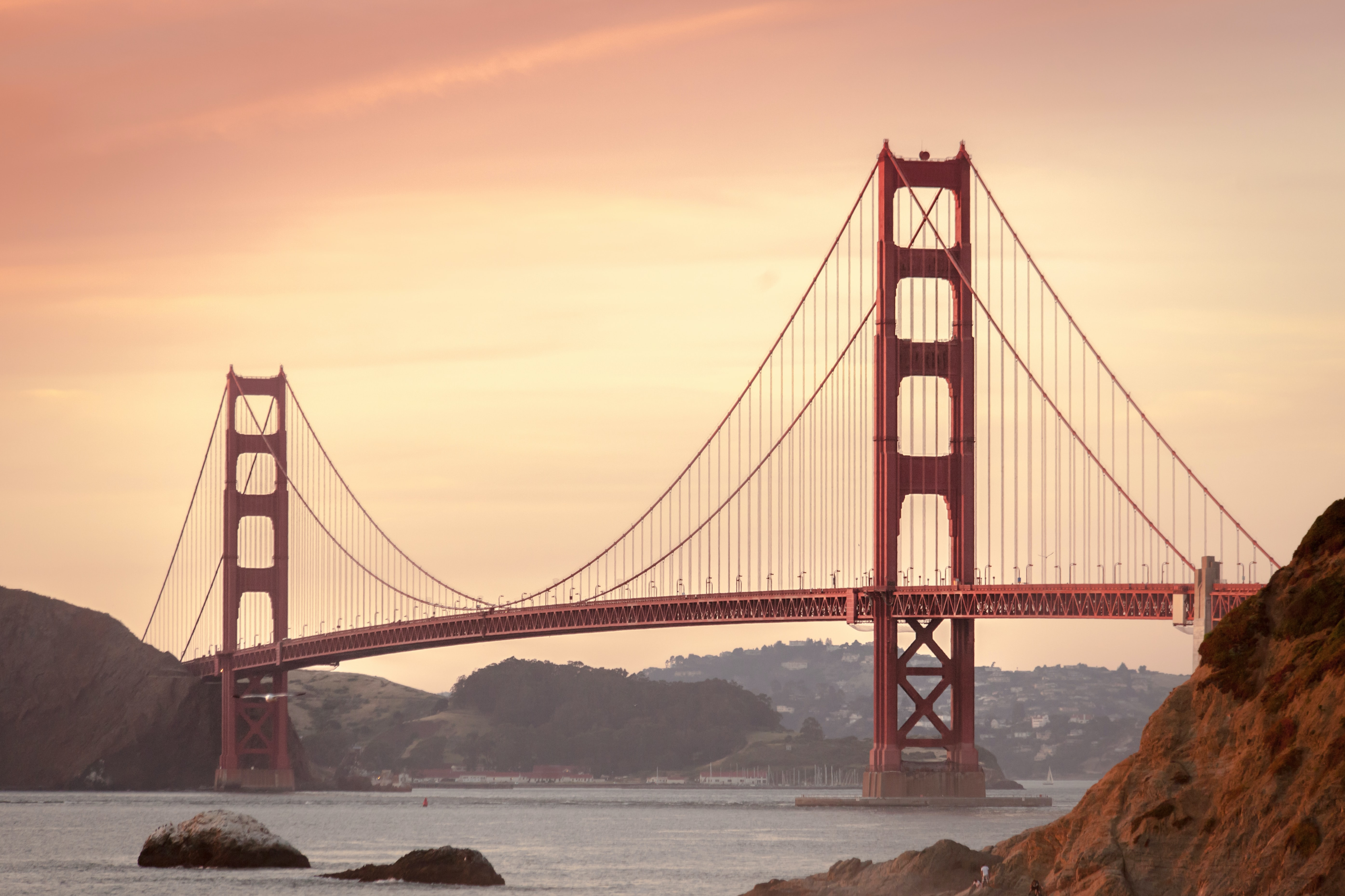 Golden Gate Bridge in San Francicso with a dusky orange sunset and haze.