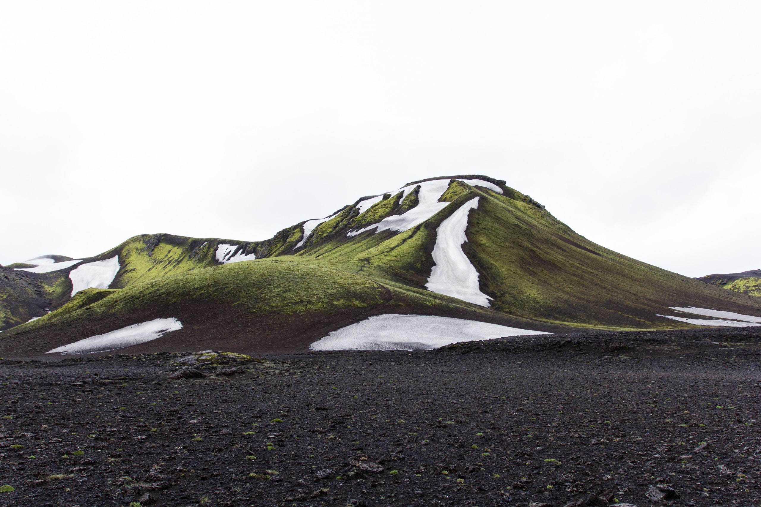 green mountain under white sky