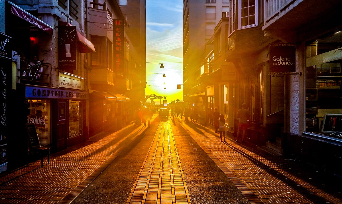 A walking street of shops glowing in the sun at sunset or sunrise