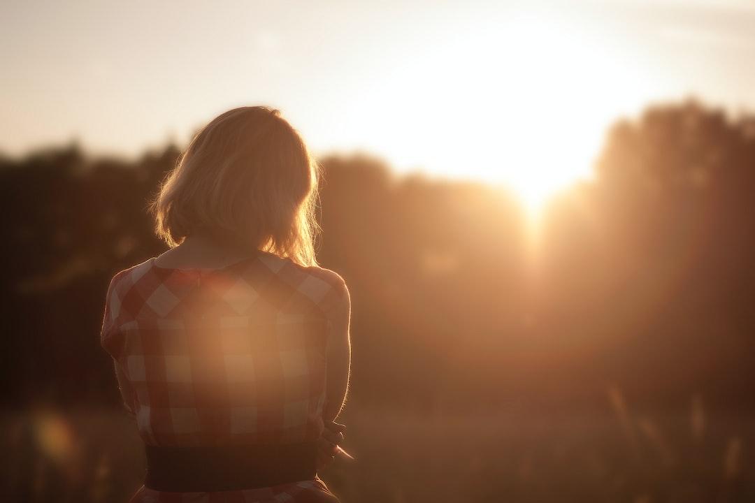 Woman contemplates sunrise.