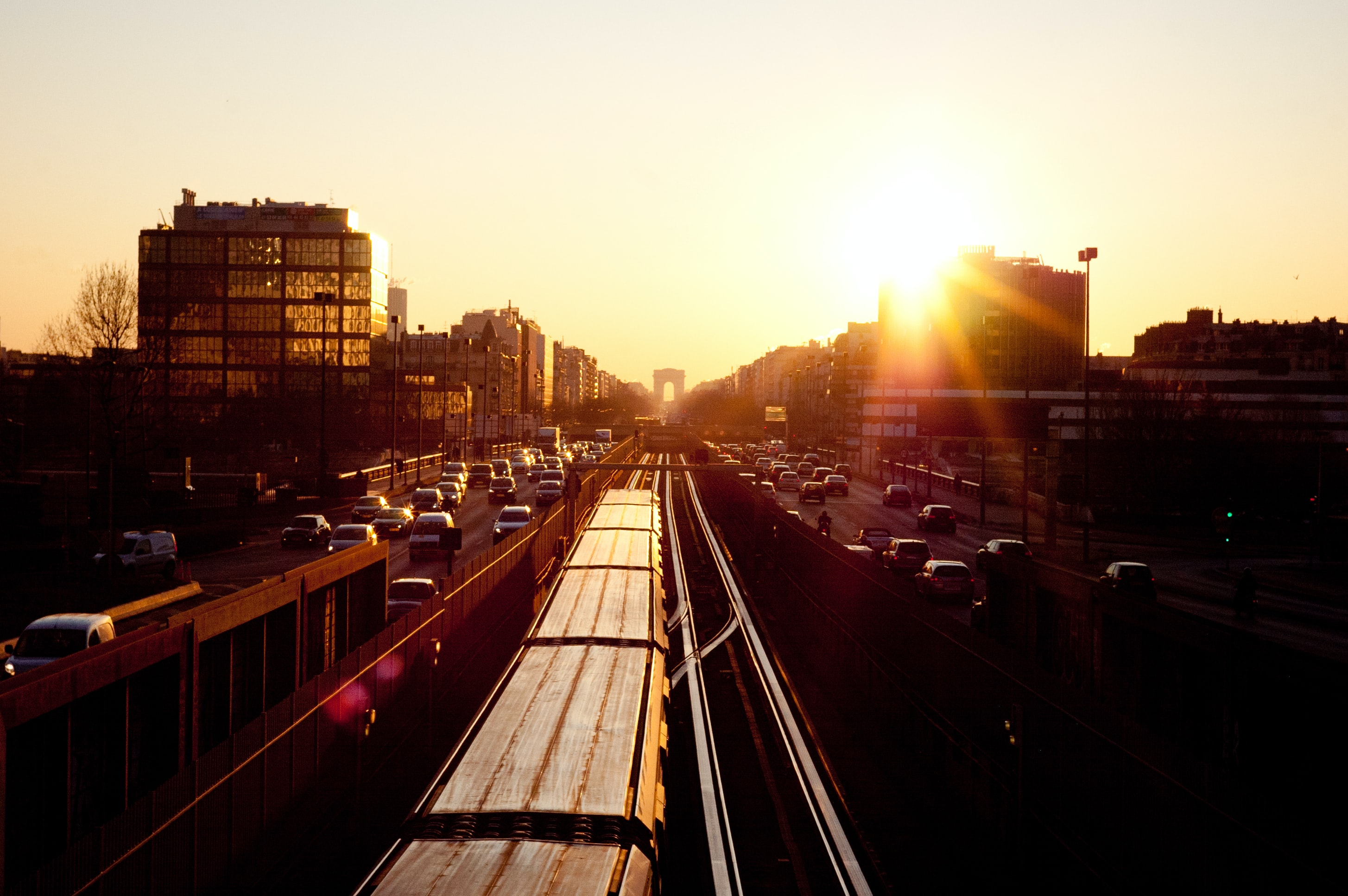 Sunset shines over busy freeway as traffic flows through lanes