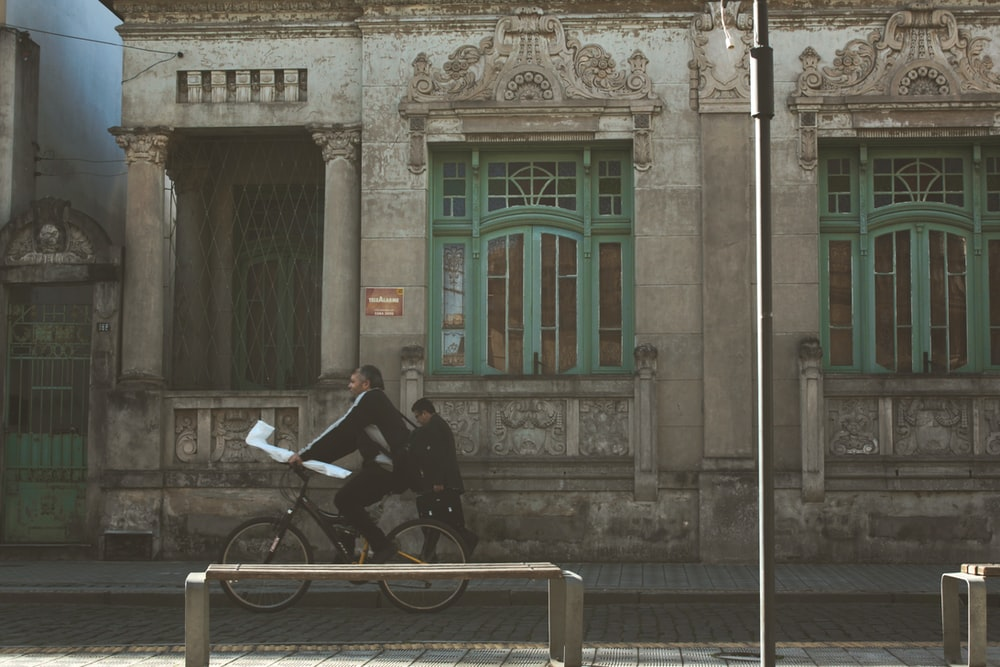 man riding bicycle on the street during daytime