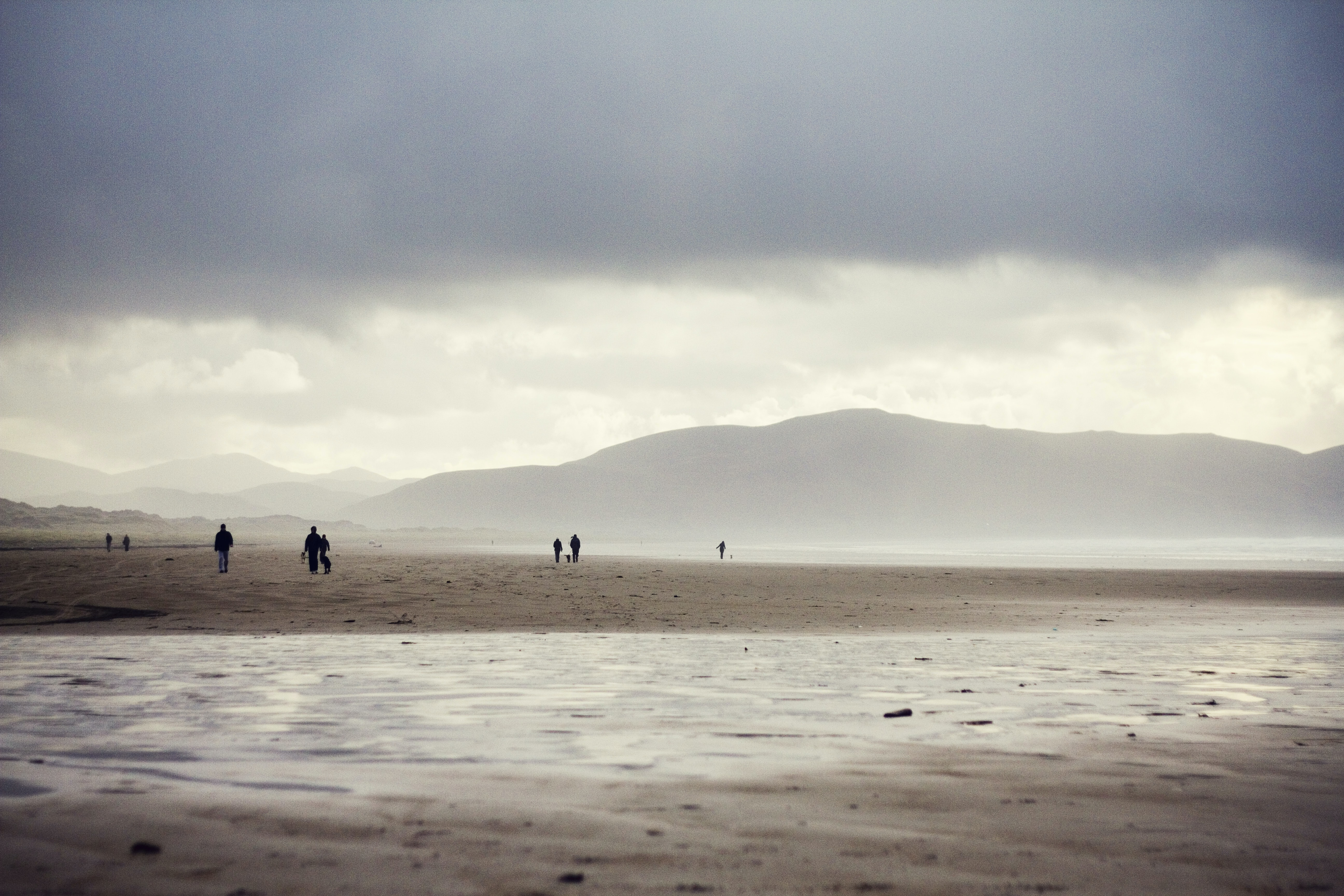 People walking on the sand along a high tide shore in a cloudy day.