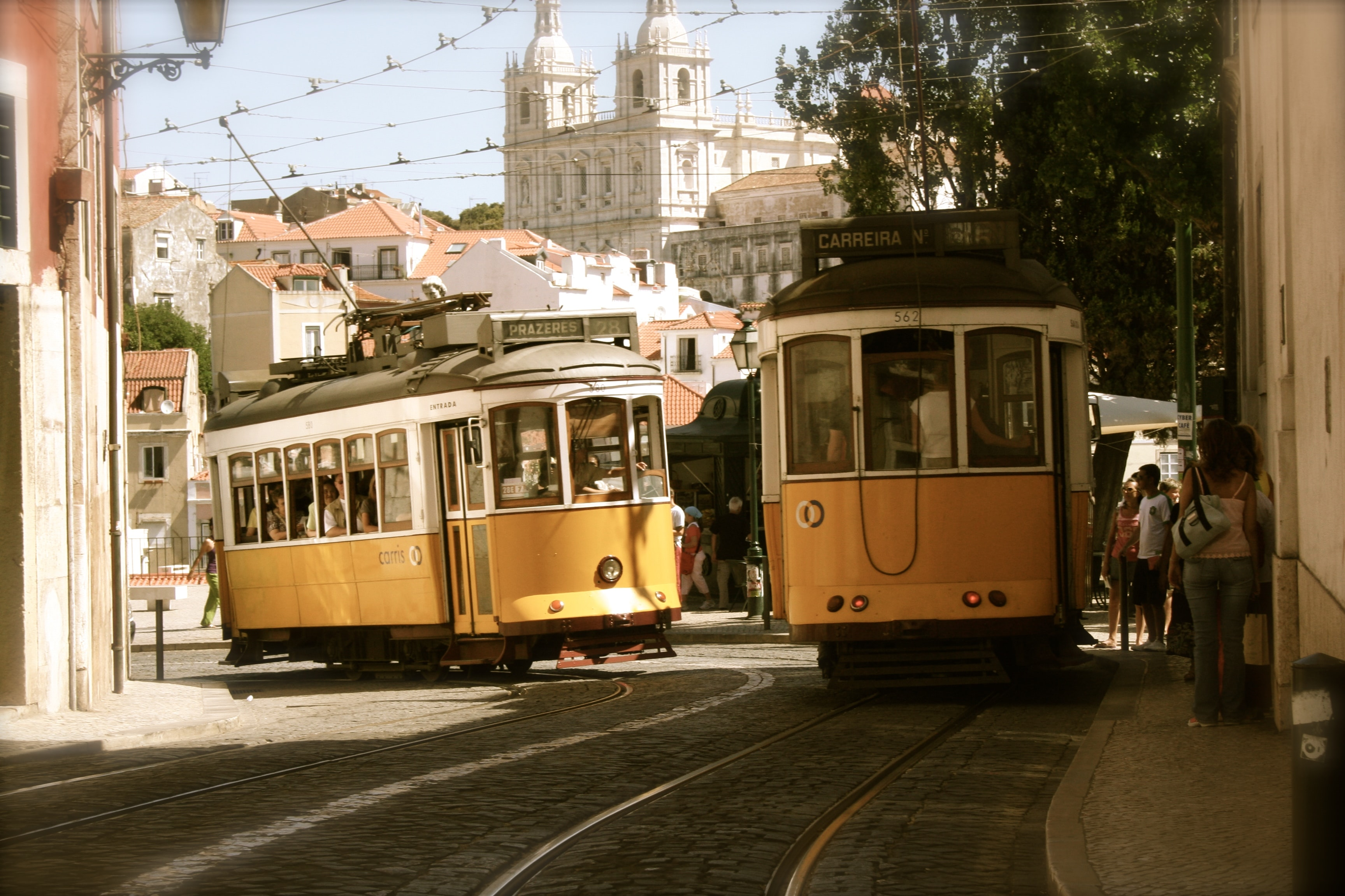 Trolley cars on rails on a side street in a sunlit Portuguese city