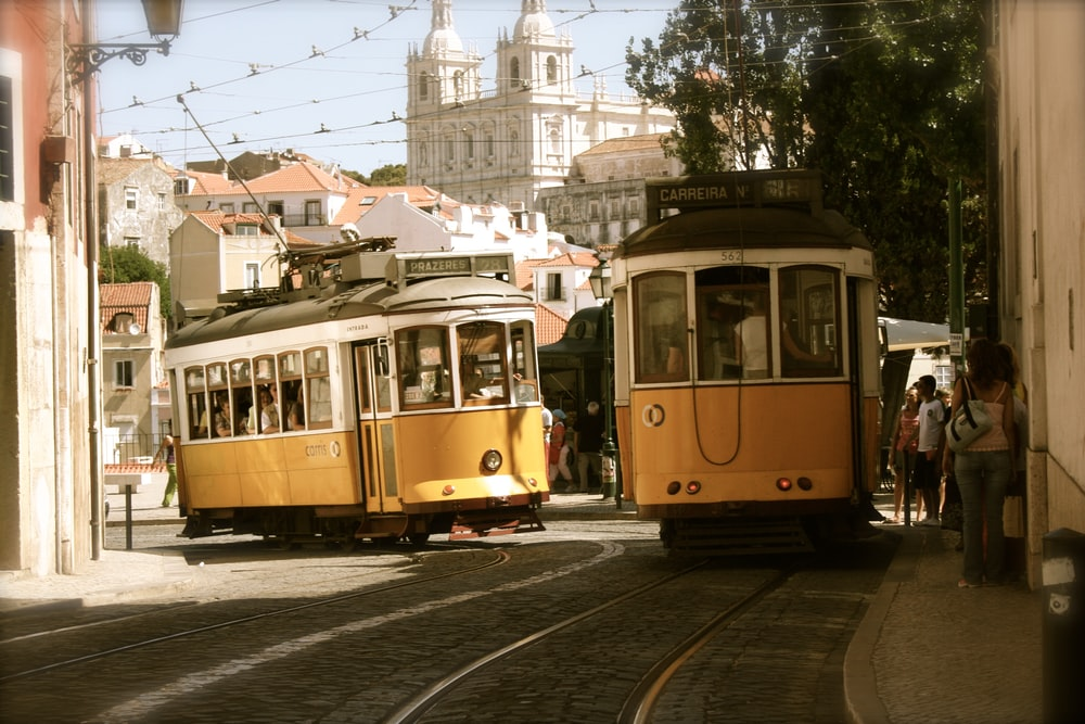 two yellow-and-white trams