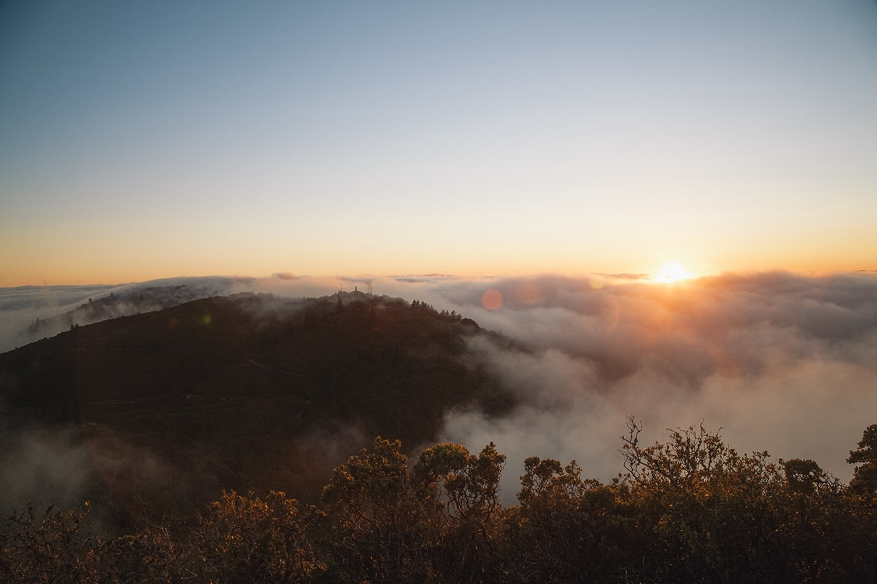 A scenic landscape with thick fog shrouding wooded hills during sunrise