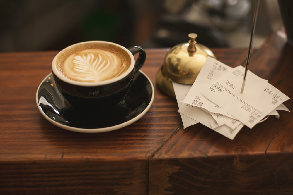black ceramic cup with saucer and cappuccino on brown wooden surface