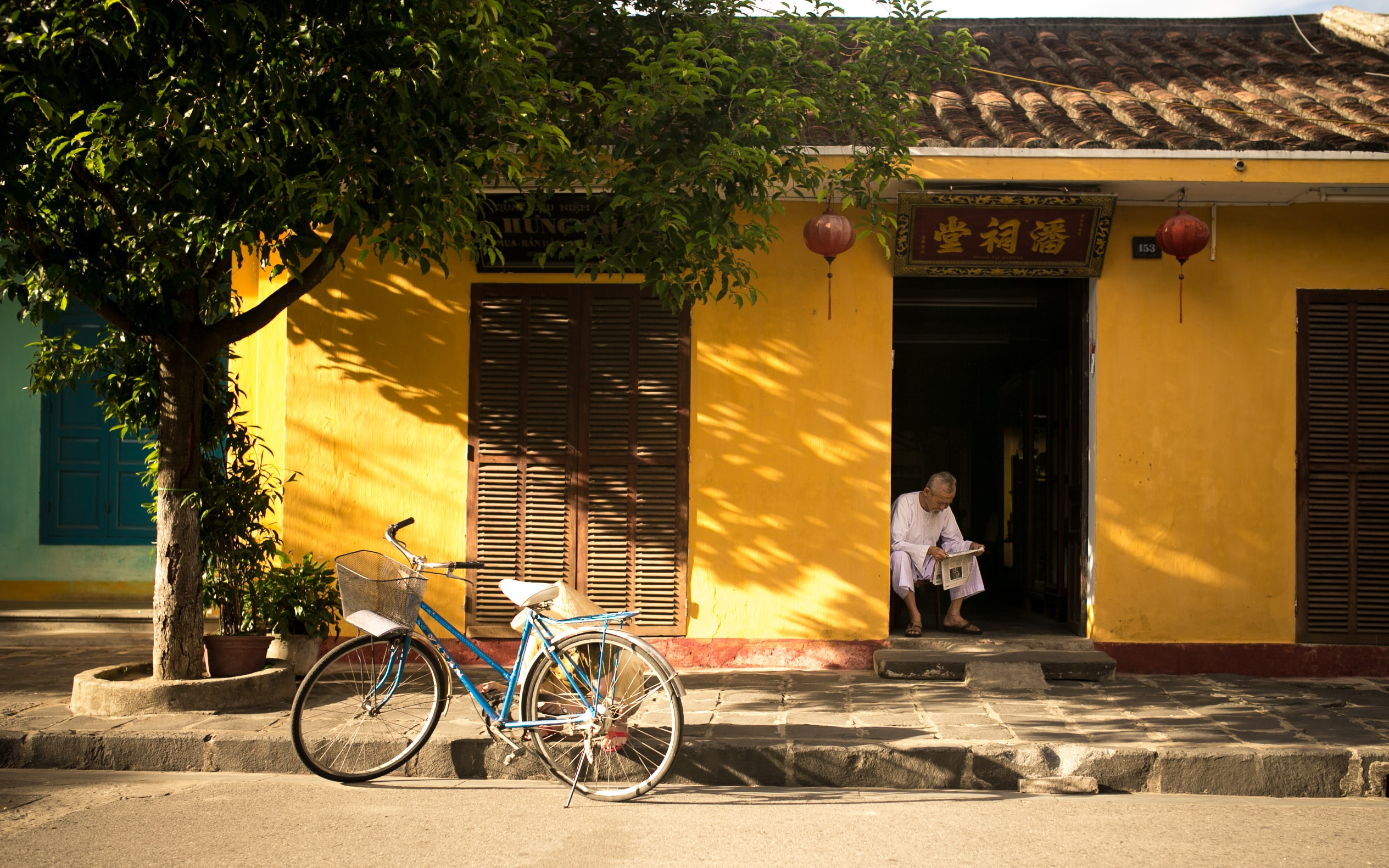 A man sitting on his stoop reading the newspaper and a bicycle leaning on a tree in Asia