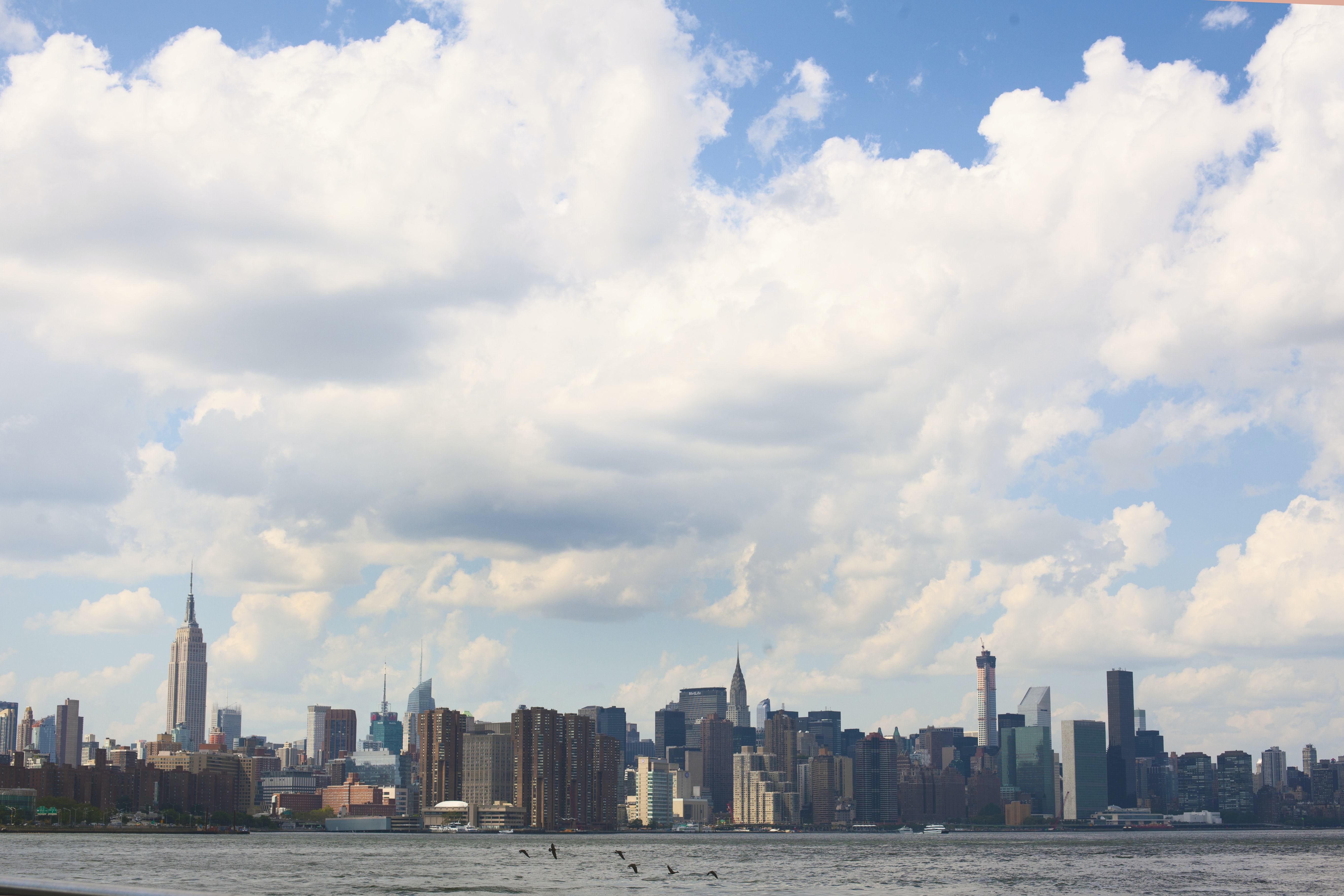 Fluffy, white clouds cover the New York City skyline and the river