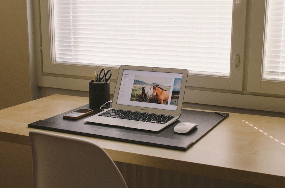 turned on MacBook on beige wooden desk