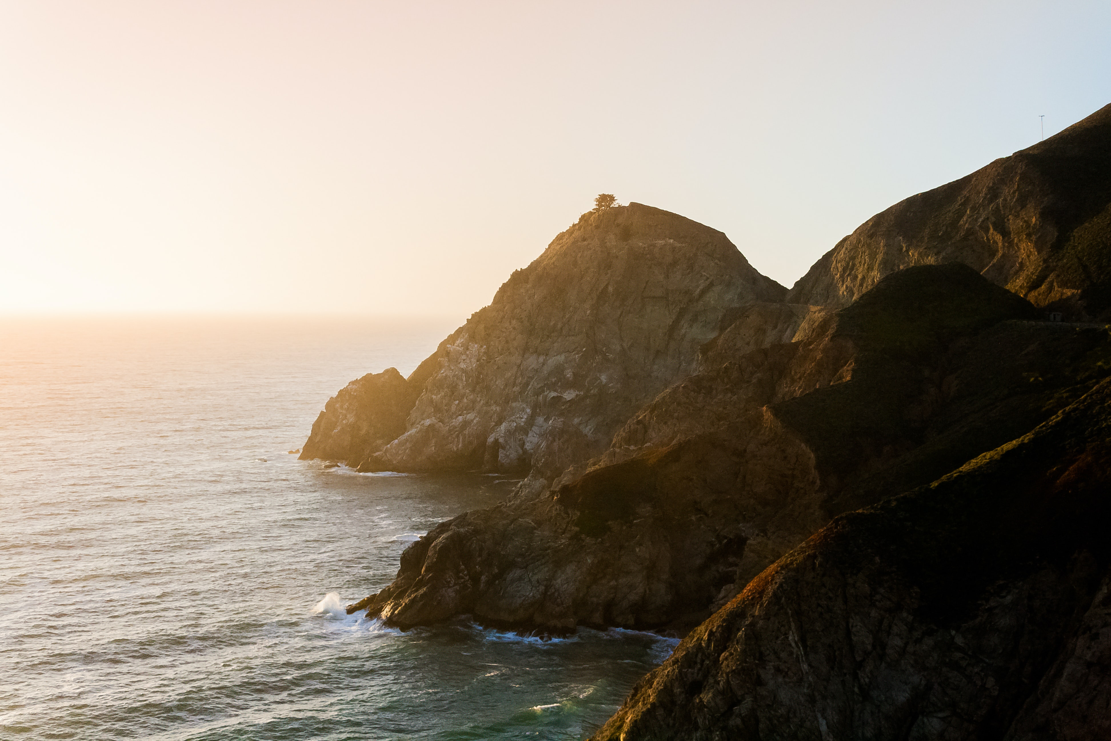 Mountains and cliff near the sea and ocean over a sunrise and the coast.