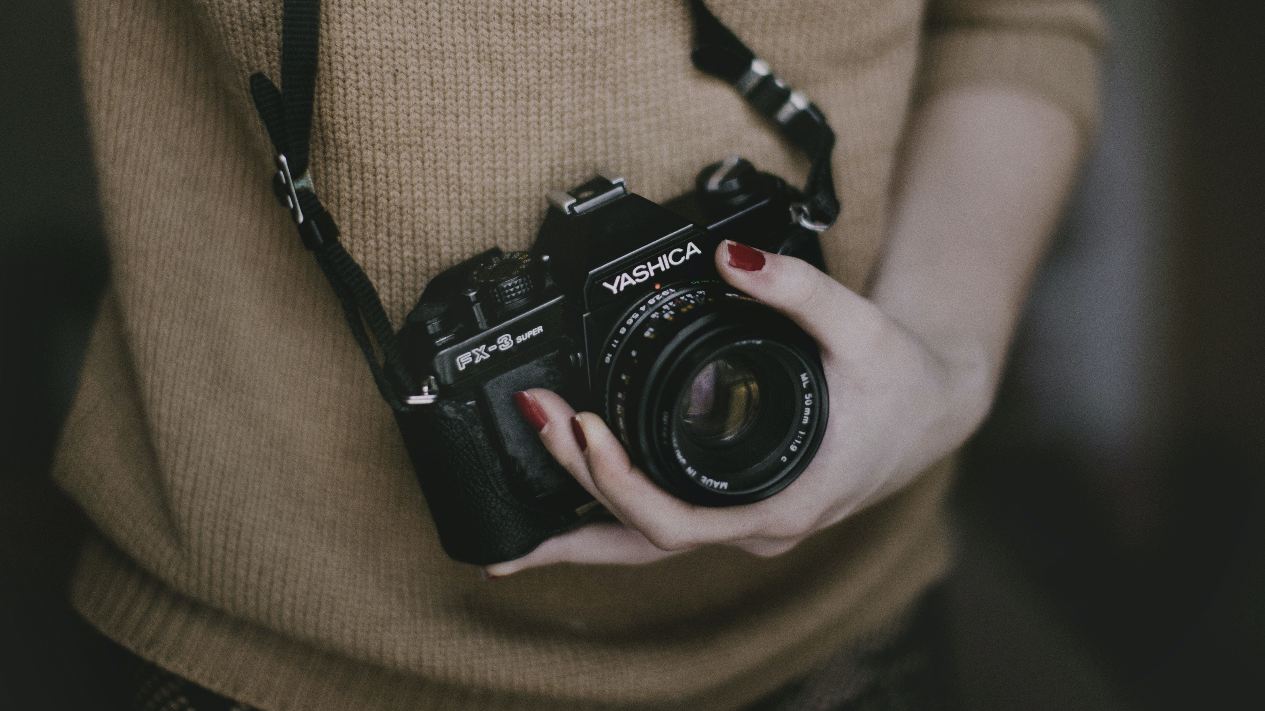 A woman holding a vintage Yashica camera.