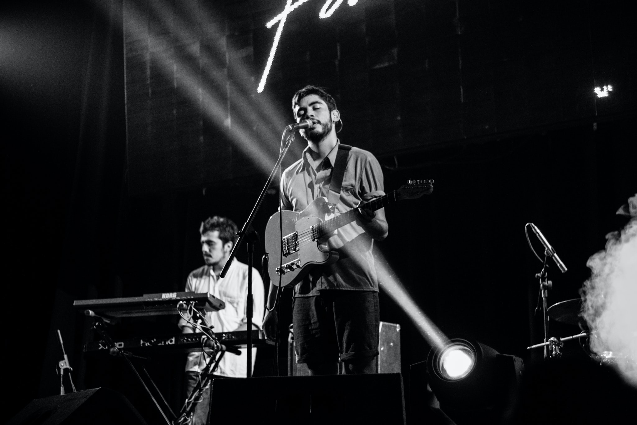A black-and-white photo of a male singer holding a guitar with a keyboard player in the background