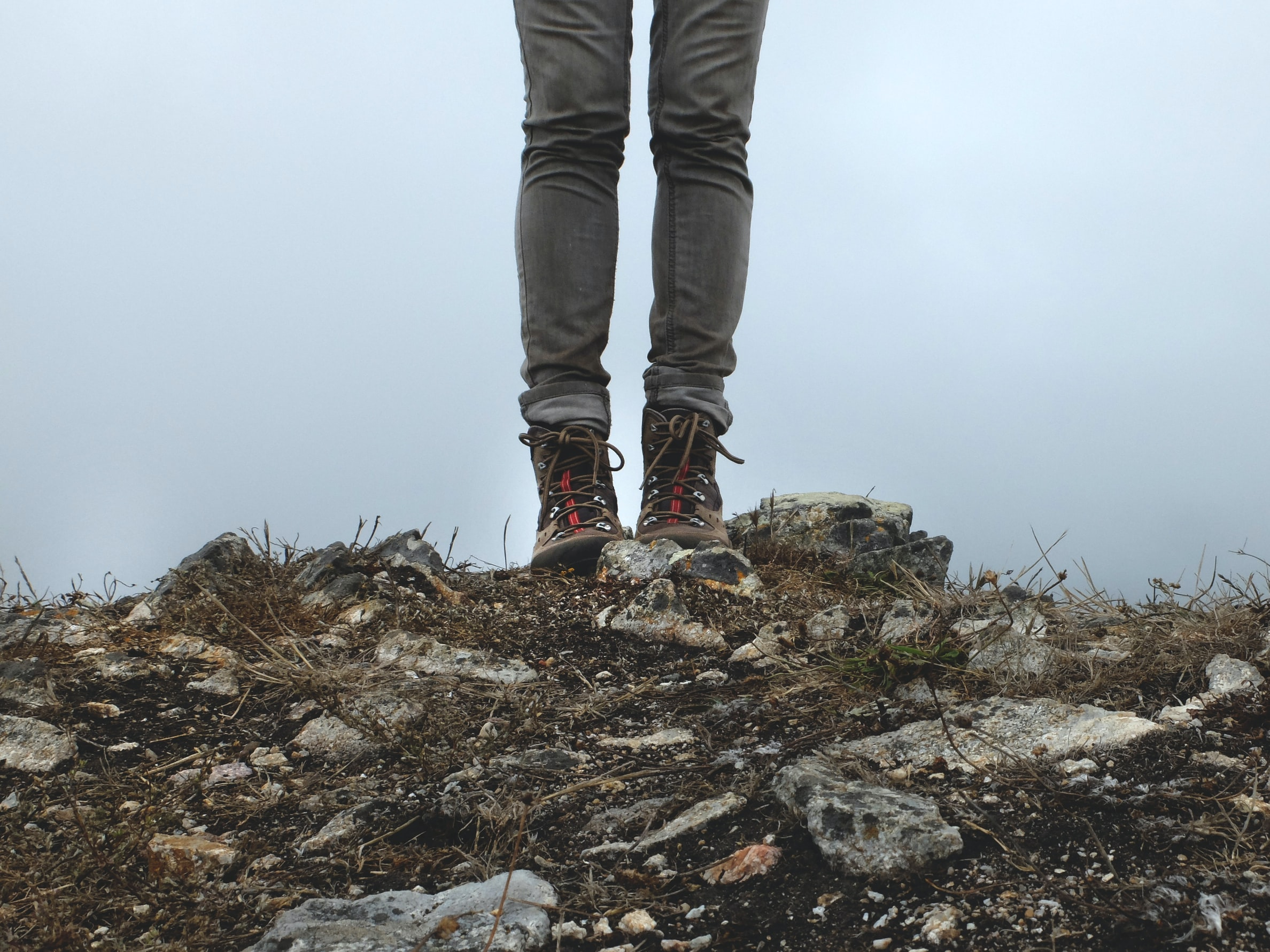 person in gray jeans standing on rocks during daytime