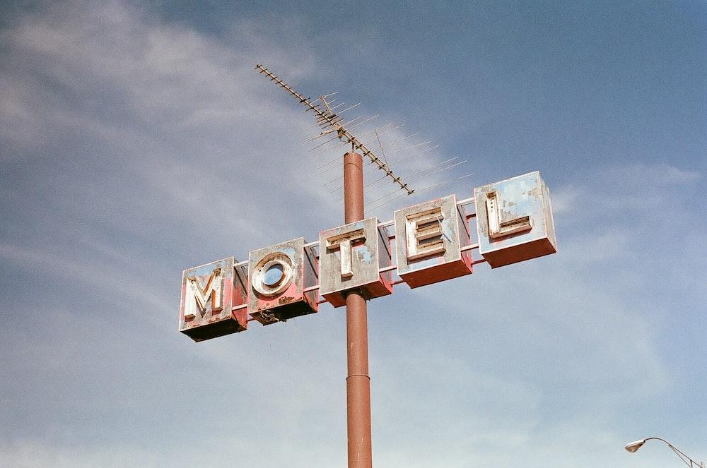brown metal Motel road sign at daytime